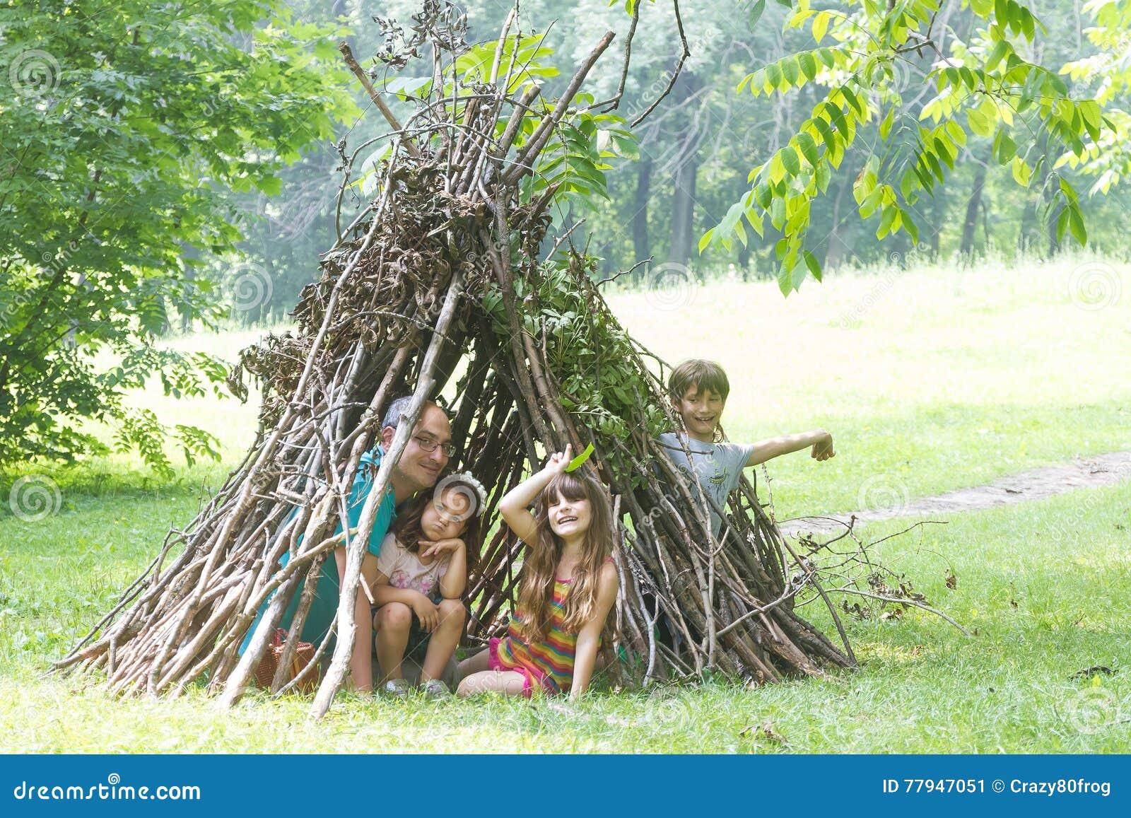 Παιδιά που παίζουν δίπλα ξύλινο να μοιάσει σπιτιών ραβδιών με την ινδική καλύβα,