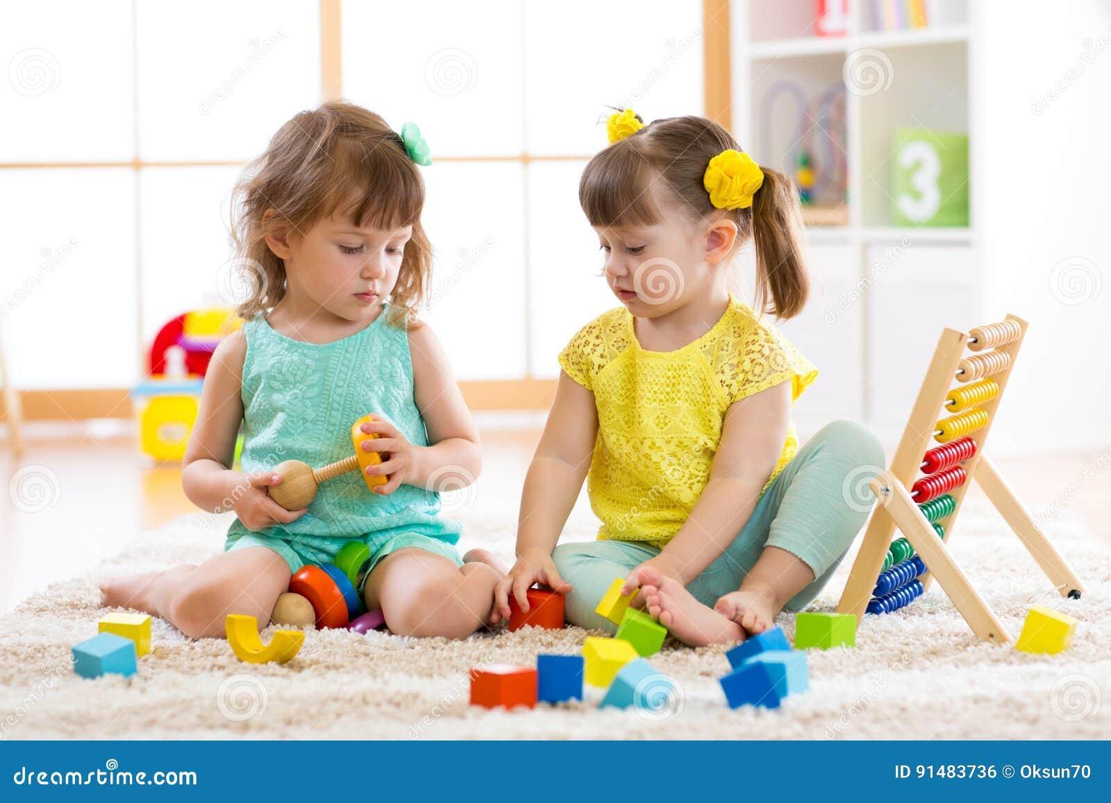 Παιδιά που παίζουν μαζί με τις δομικές μονάδες Εκπαιδευτικά παιχνίδια για τα παιδιά παιδικών σταθμών και παιδικών σταθμών Τα μικρ