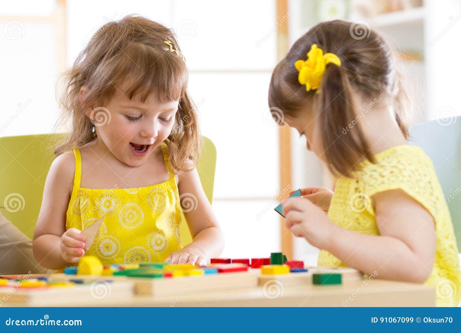Παιδιά που παίζουν με τα ζωηρόχρωμα παιχνίδια φραγμών Δύο κορίτσια παιδιών στο σπίτι ή κέντρο φύλαξης Εκπαιδευτικά παιχνίδια παιδ