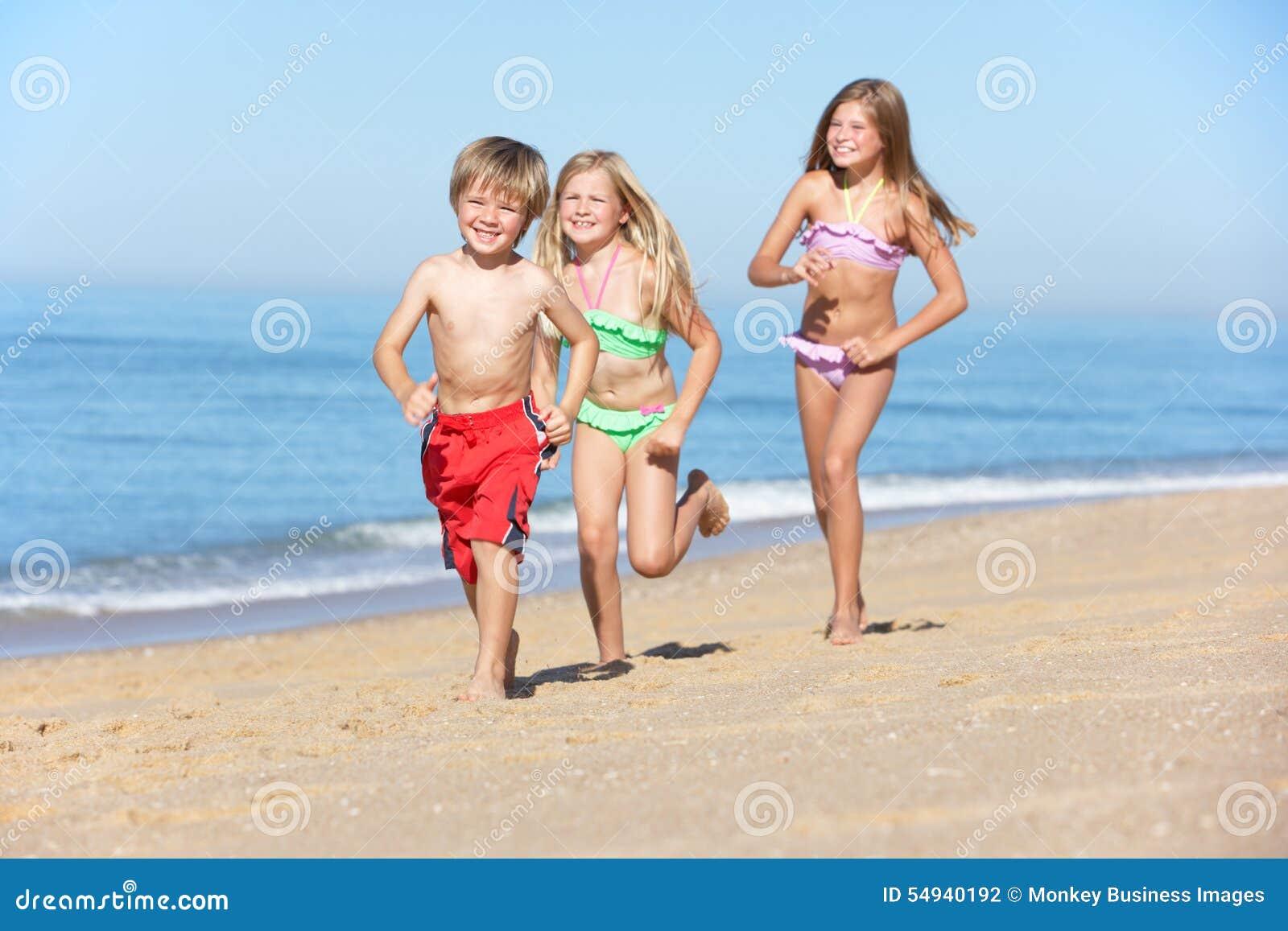 Παιδιά που τρέχουν κατά μήκος της θερινής παραλίας