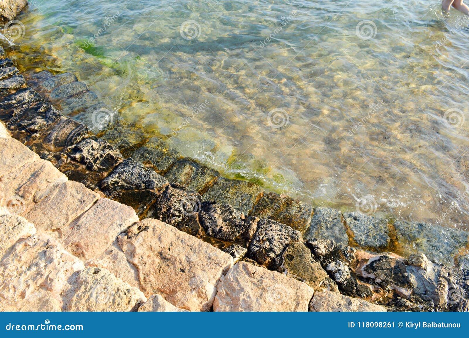 Παλαιά αρχαία κίτρινα βήματα πετρών που καλύπτονται με την πράσινη λάσπη και τη λάσπη, κάθοδος στη θάλασσα, λίμνη, ωκεανός και θα