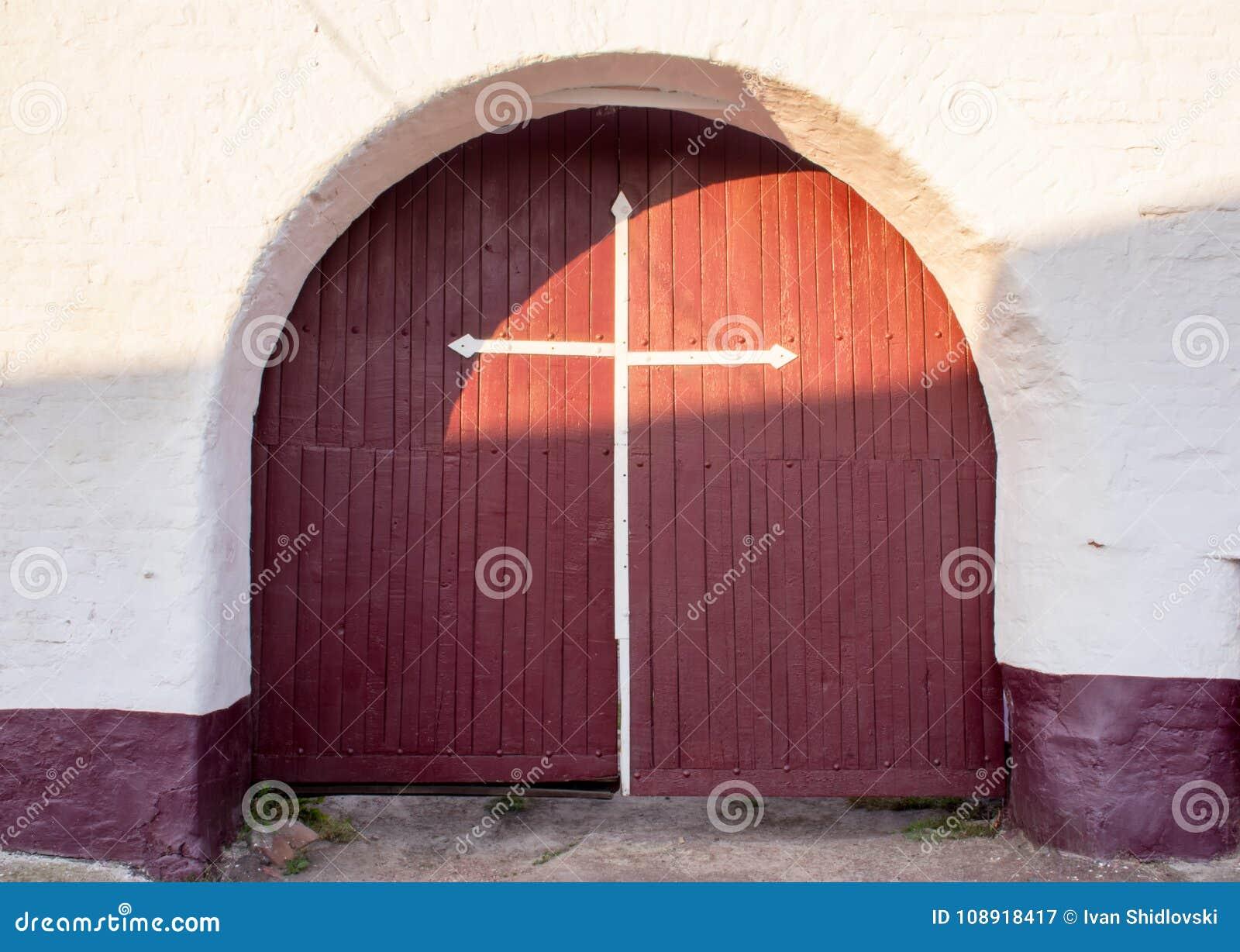 Παλαιά αρχαία πόρτα πυλών εισόδων καφέ με έναν άσπρο σταυρό σε τους ενάντια σε έναν στερεό άσπρο τουβλότοιχο Είσοδος στα χριστιαν