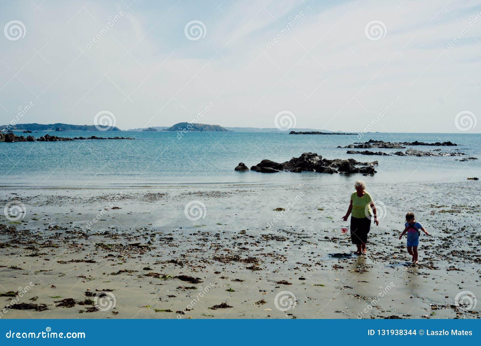 παλαιά ηλικιωμένη ανώτερη γιαγιά γυναικών που συλλέγει τα κοχύλια θάλασσας με τη μεγάλη κόρη της