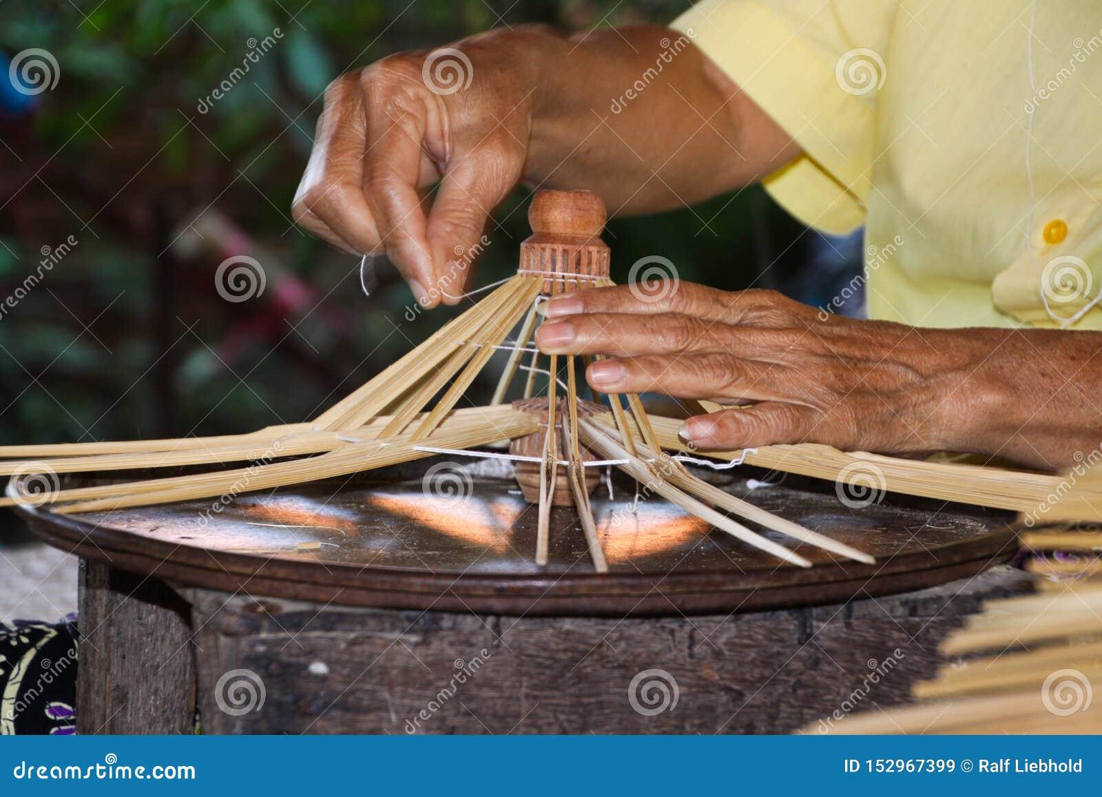 Παλαιά μεμβρανοειδή χέρια που παράγουν τα πλαίσια για τις ομπρέλες εγγράφων σε Chiang Mai