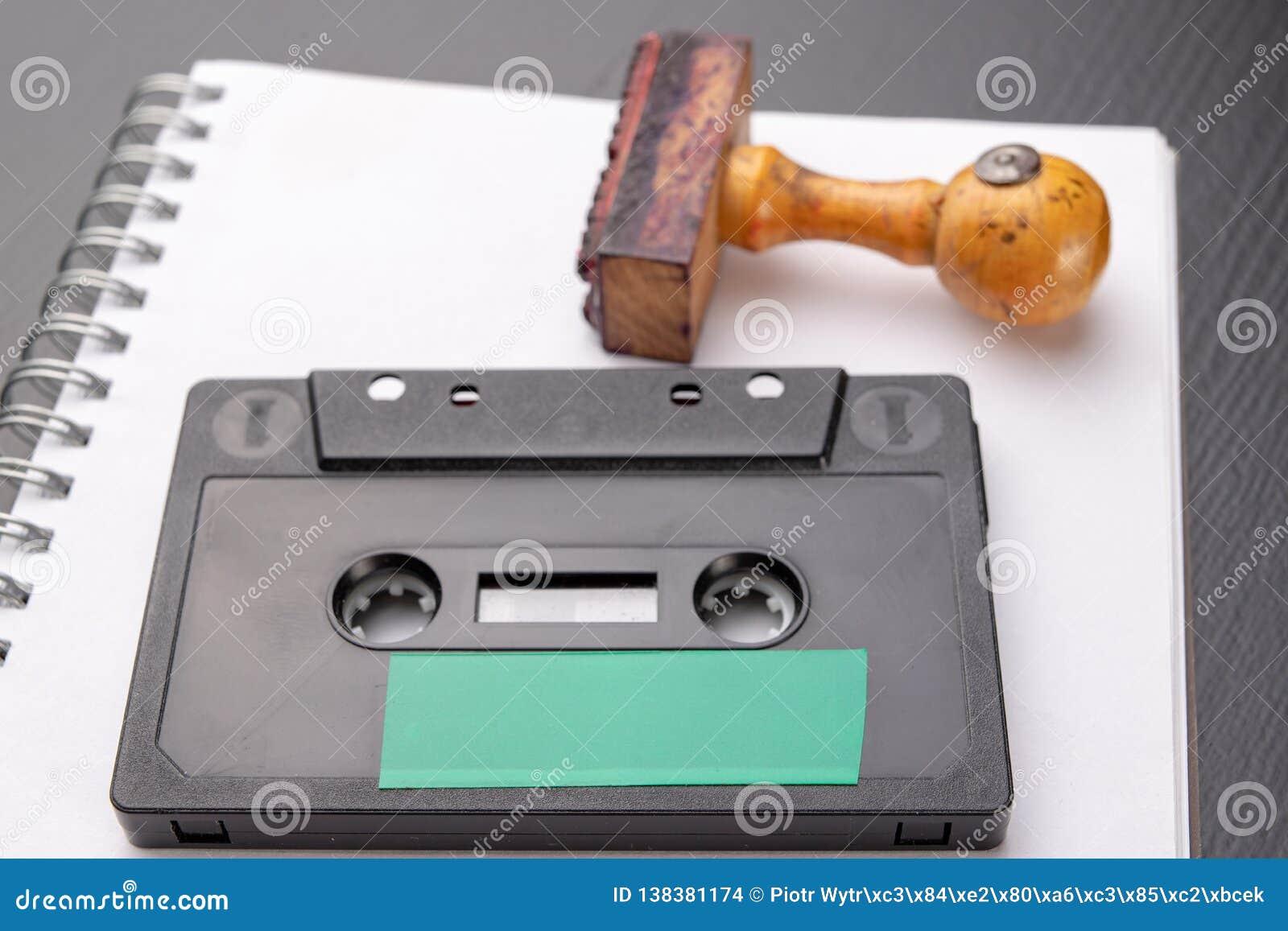 Παλαιά ξύλινη σφραγίδα και ακουστική κασέτα σε ένα άσπρο κομμάτι του σημειωματάριου Μυστικές καταγραφές των πολιτικών συζητήσεων