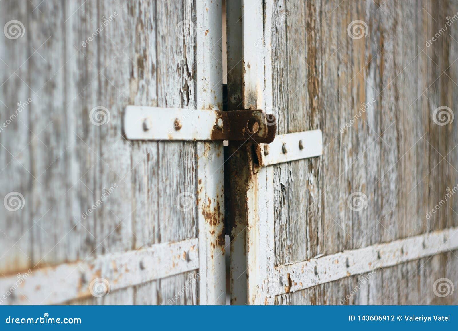 Παλαιά πύλη με το σκουριασμένο σύρτη και το χρωματισμένο λευκό