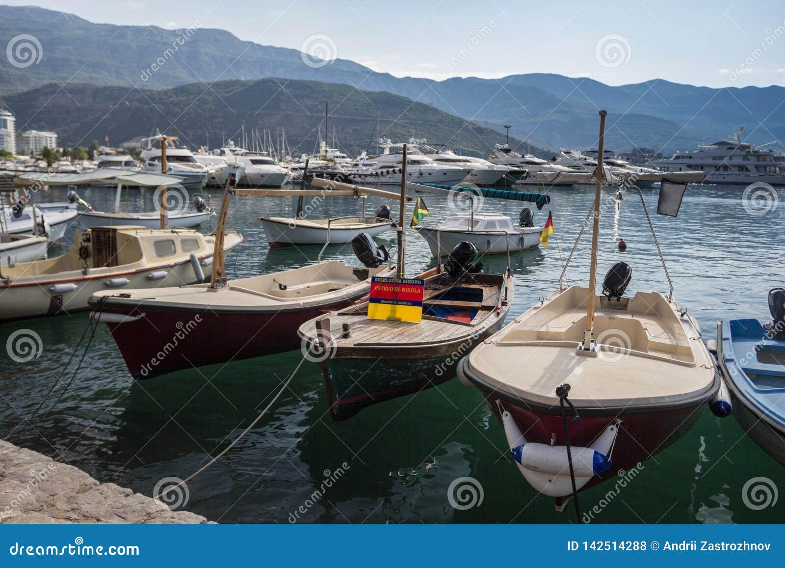 Παλαιές βάρκες στην αποβάθρα στο υπόβαθρο των βουνών και των γιοτ