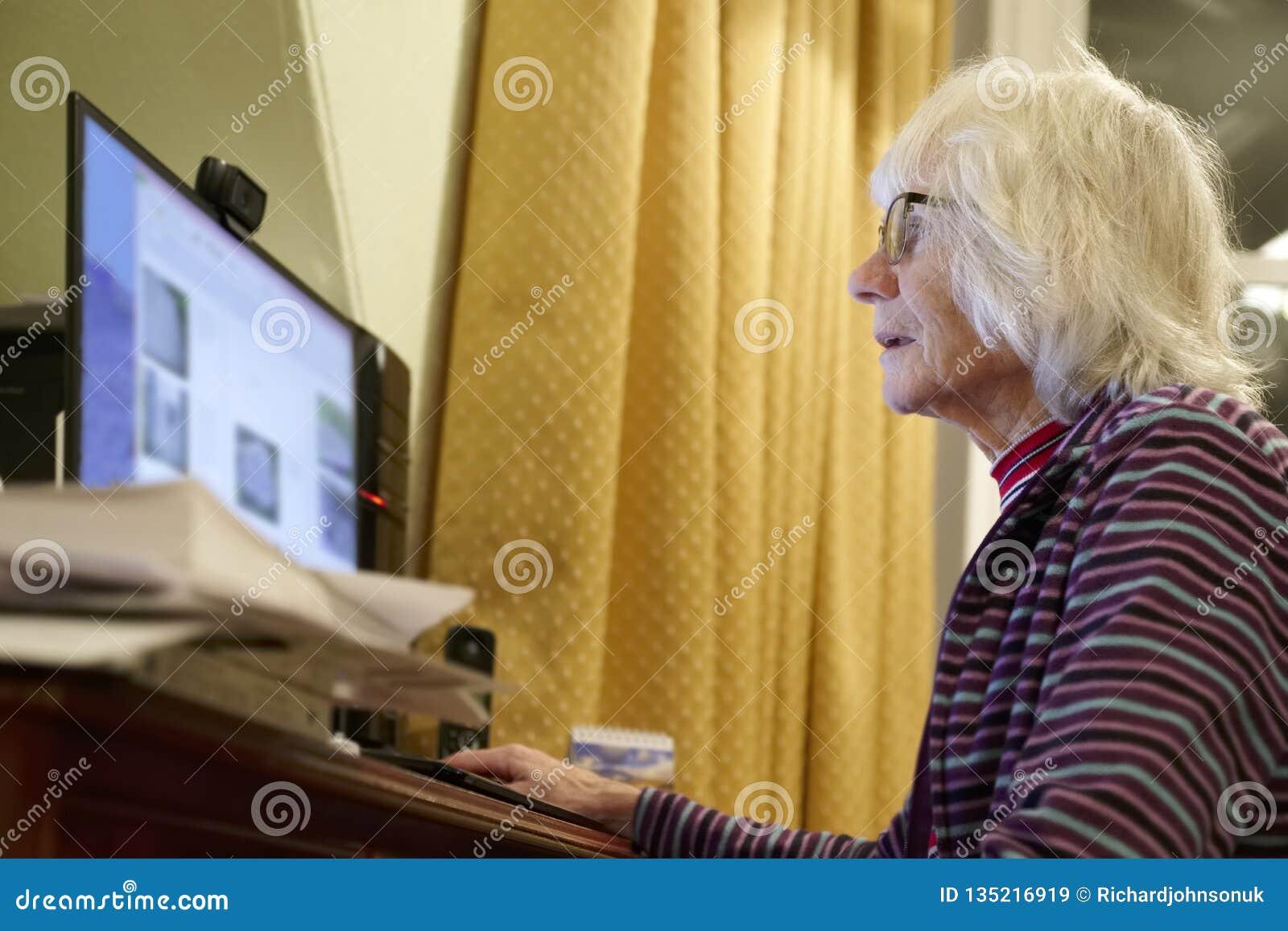 Παλαιός ηλικιωμένος ανώτερος υπολογιστής εκμάθησης προσώπων και σε απευθείας σύνδεση απάτη απάτης χρημάτων δεξιοτήτων Διαδικτύου