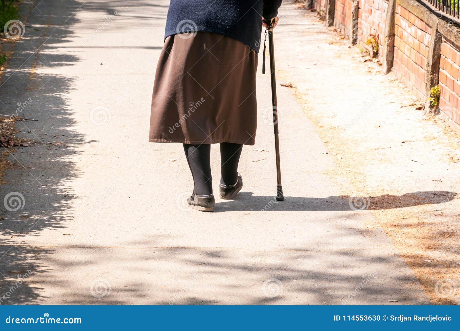 Παλαιός καταθλιπτικός περίπατος γυναικών μόνο κάτω από την οδό με τη μόνη και χαμένη άποψη συναισθήματος ραβδιών ή καλάμων περπατ
