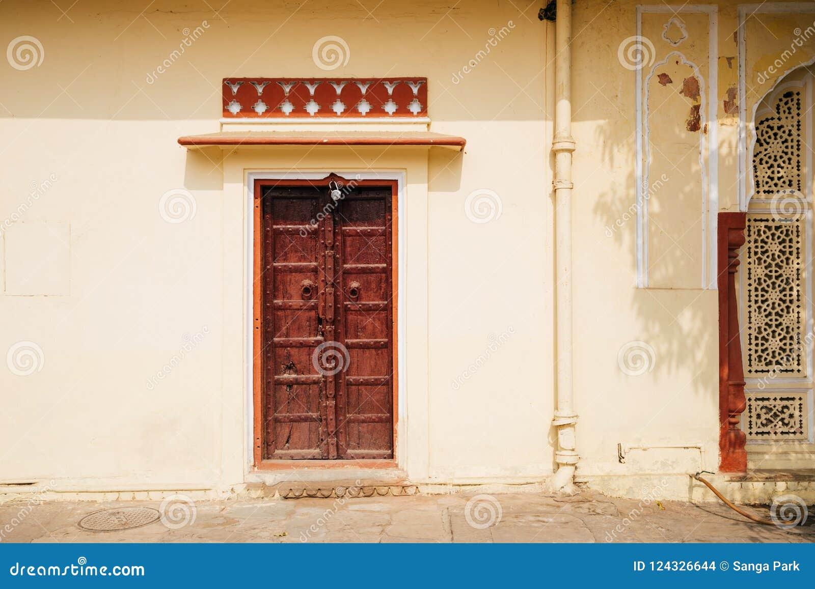 Παλαιός τοίχος και ξύλινη πόρτα στο παλάτι πόλεων στο Jaipur, Ινδία