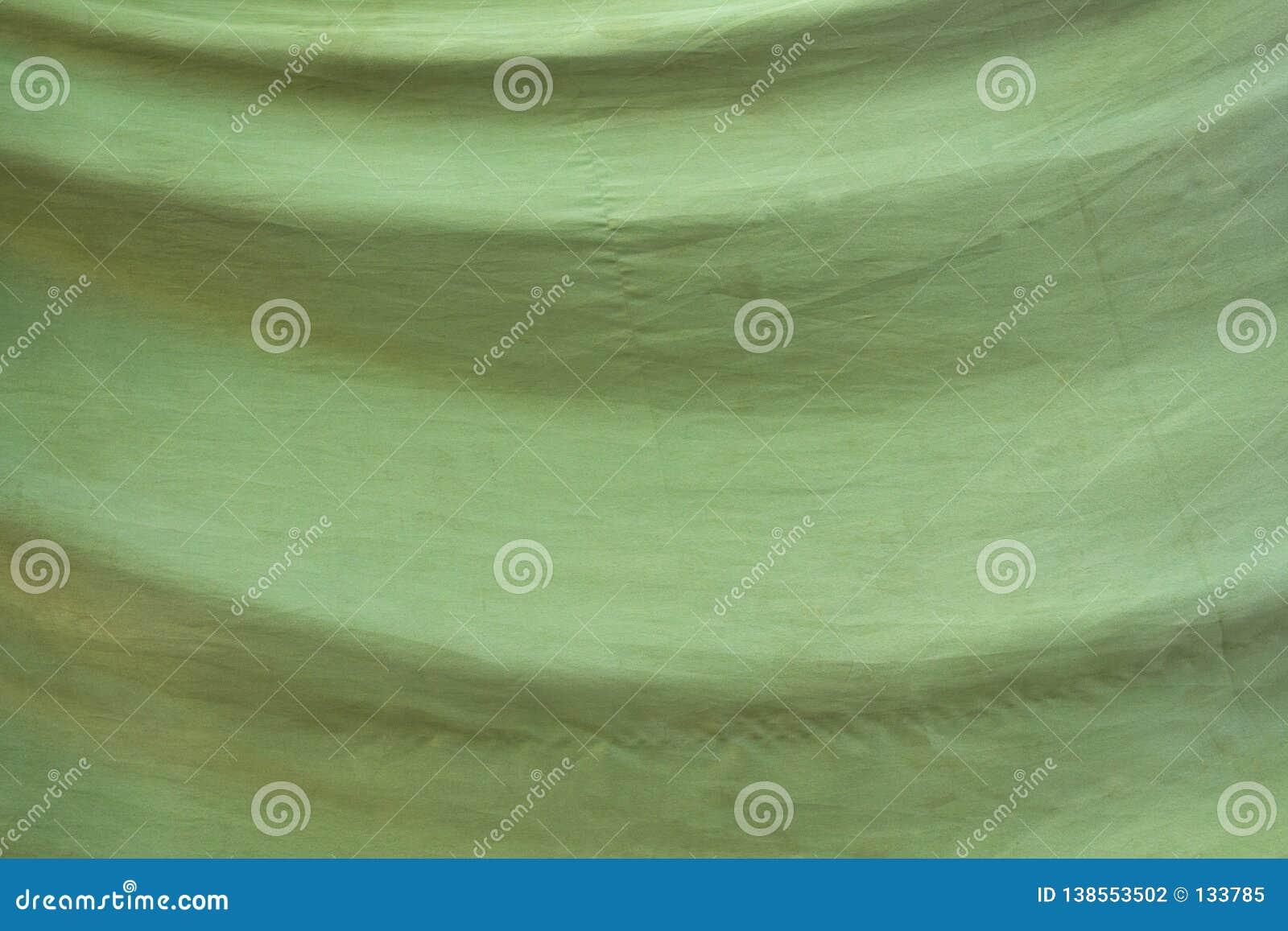 Παλαιό εξασθενισμένο πράσινο ύφασμα με τις πτυχές Σύσταση τραχιάς επιφάνειας