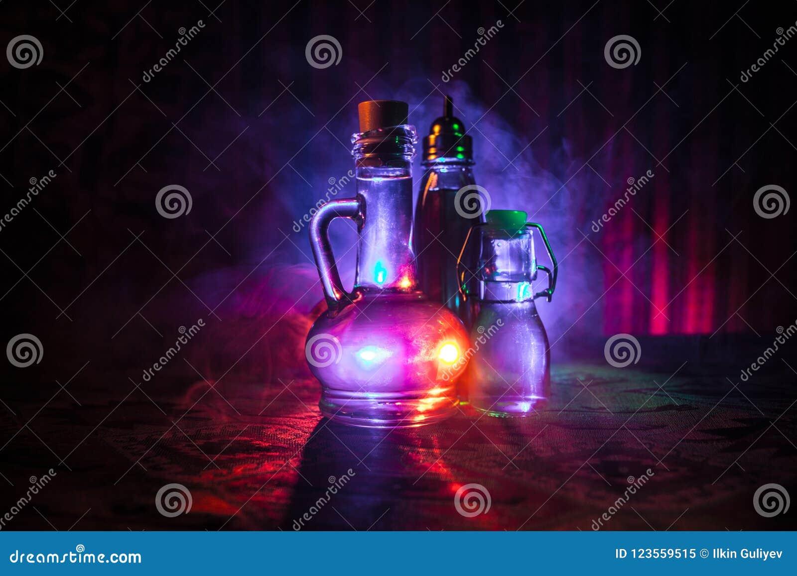 Παλαιό και εκλεκτής ποιότητας μπουκάλι γυαλιού στο σκοτεινό ομιχλώδες υπόβαθρο με το φως Δηλητήριο ή μαγική υγρή έννοια