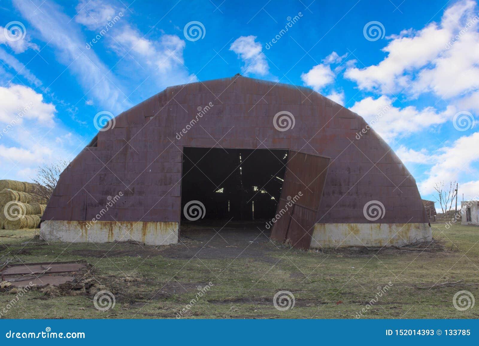 Παλαιό καφετί σκουριασμένο υπόστεγο μετάλλων με τις ανοικτές σπασμένες πύλες κάτω από έναν φωτεινό μπλε ουρανό με τα άσπρα σύννεφ