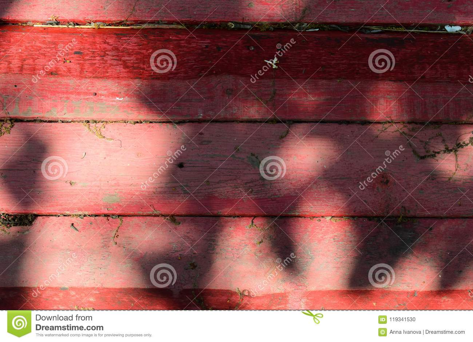Παλαιό ξύλινο υπόβαθρο φιαγμένο από οριζόντιους πίνακες, που χρωματίζονται στο κόκκινο χρώμα, με τις σκιές και το φως του ήλιου