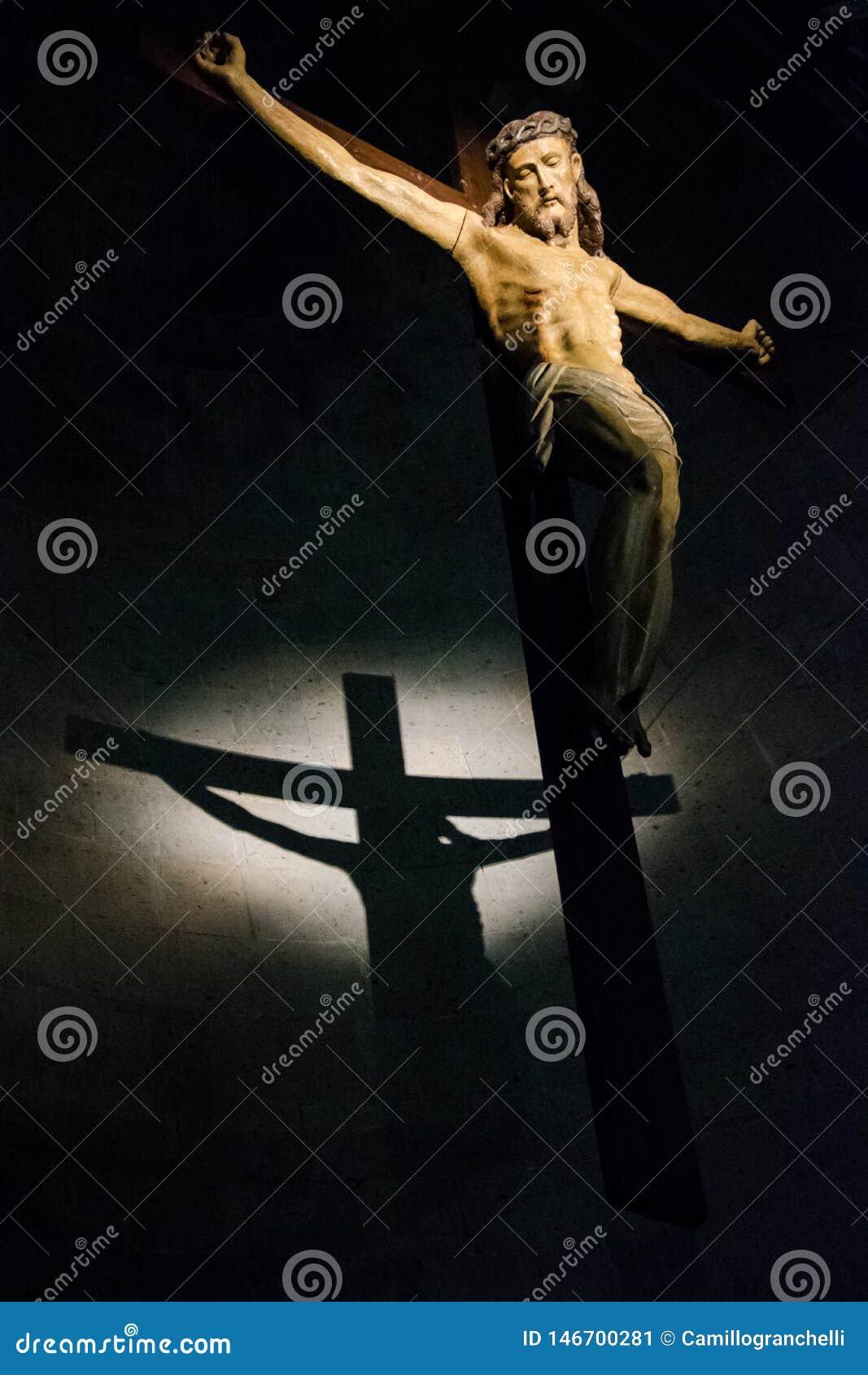 Παλαιό ξύλινο crucifix που φωτίζεται μέσα σε μια ιστορική ιταλική εκκλησία με τη σκιά που πετιέται στον τοίχο