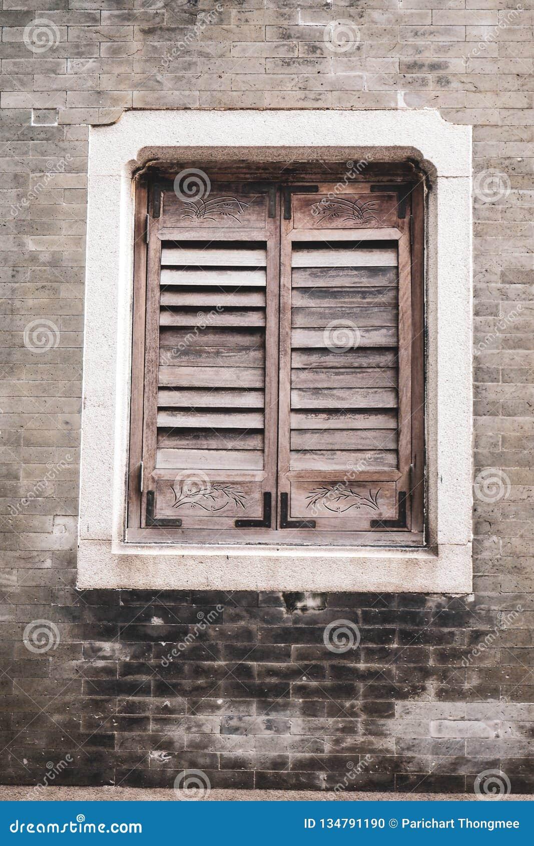 Παλαιό ξύλινο Louver παράθυρο στο τουβλότοιχο Κάθετο υπόβαθρο τούβλου ύφους παλαιό αγροτικό