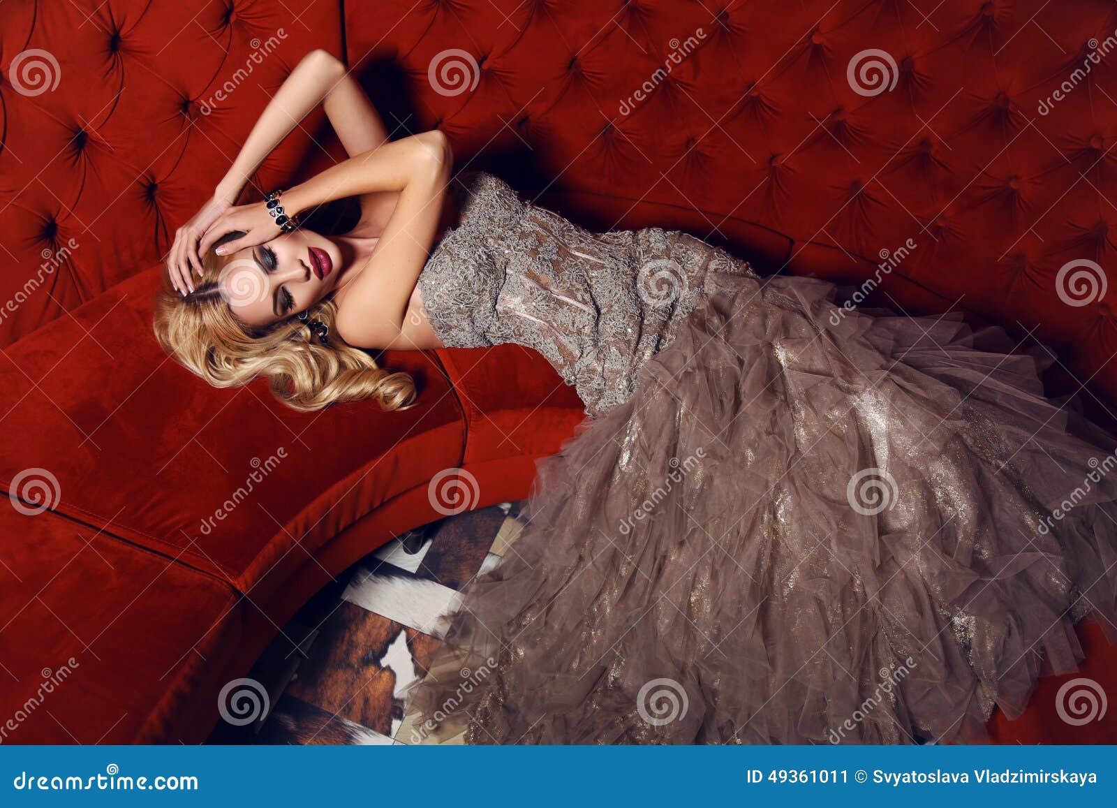Πανέμορφη γυναίκα με τα ξανθά μαλλιά στο κομψό φόρεμα που βρίσκεται στο κόκκινο ντιβάνι