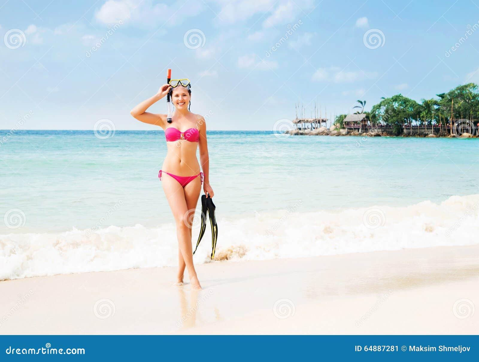 Πανέμορφη, λεπτή, εύθυμη τοποθέτηση κοριτσιών με τη μάσκα κατάδυσης και βατραχοπέδιλα seacoast στην Ταϊλάνδη