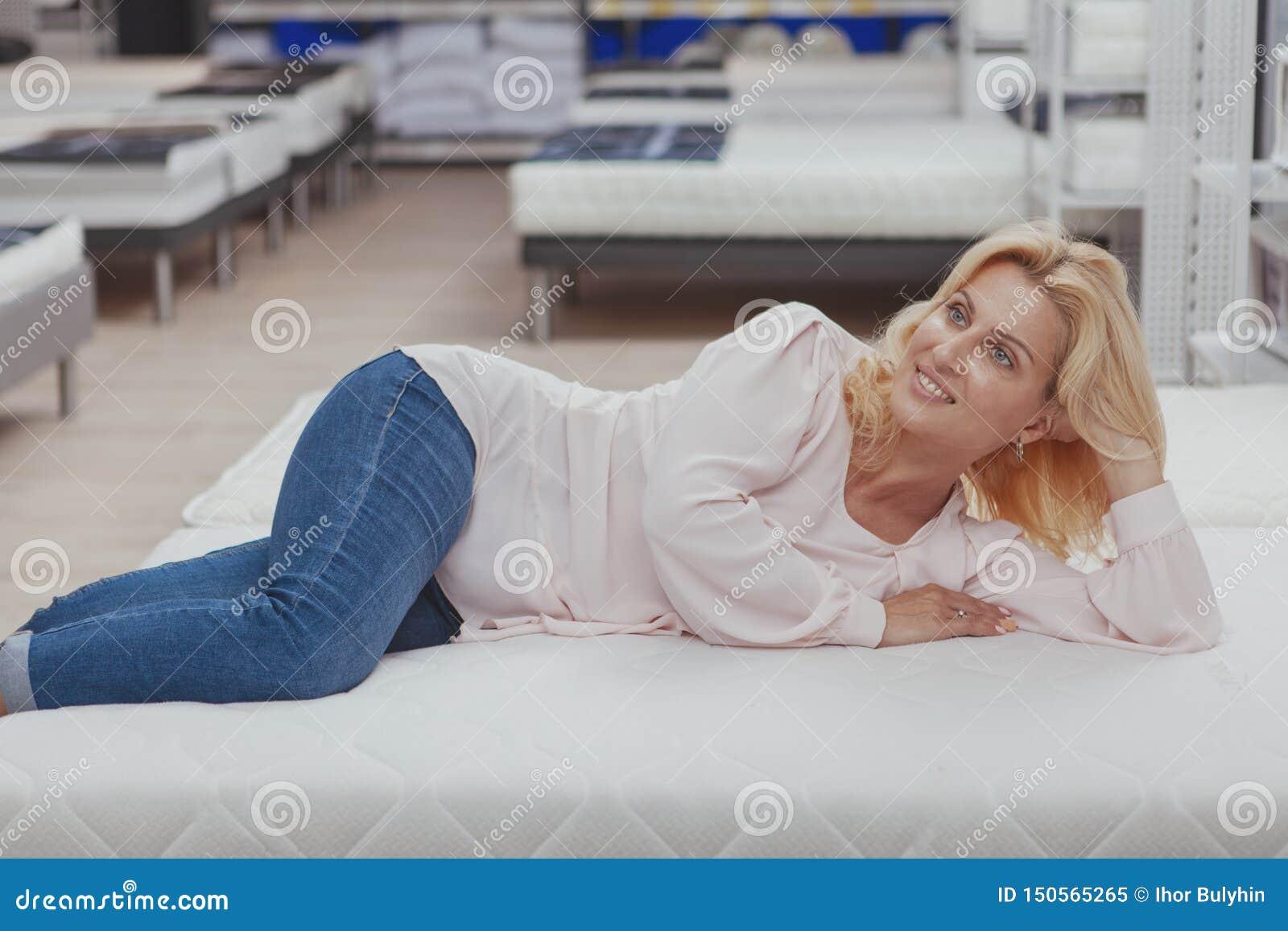 Πανέμορφη κομψή ώριμη γυναίκα που ψωνίζει για το νέο ορθοπεδικό κρεβάτι