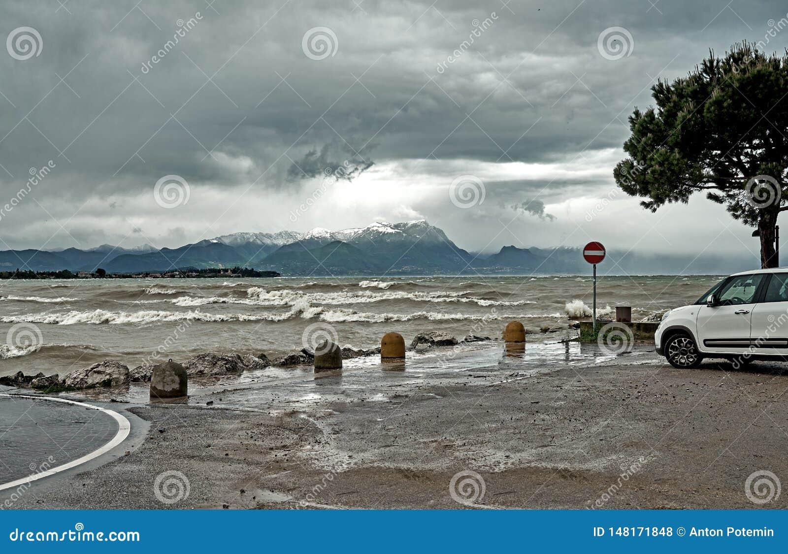 Πανέμορφη λίμνη Garda στην Ιταλία που περιβάλλεται από τα βουνά και τα θυελλώδη σύννεφα