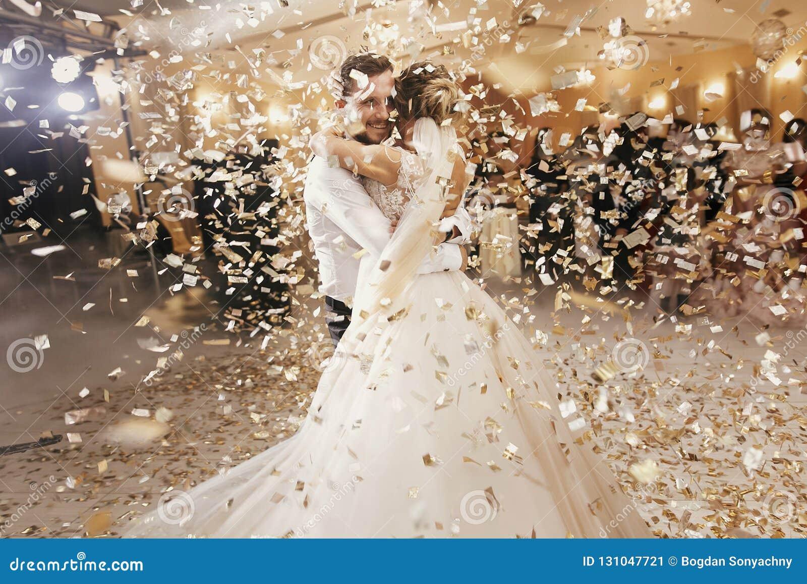 Πανέμορφη νύφη και μοντέρνος νεόνυμφος που χορεύουν κάτω από το χρυσό κομφετί α
