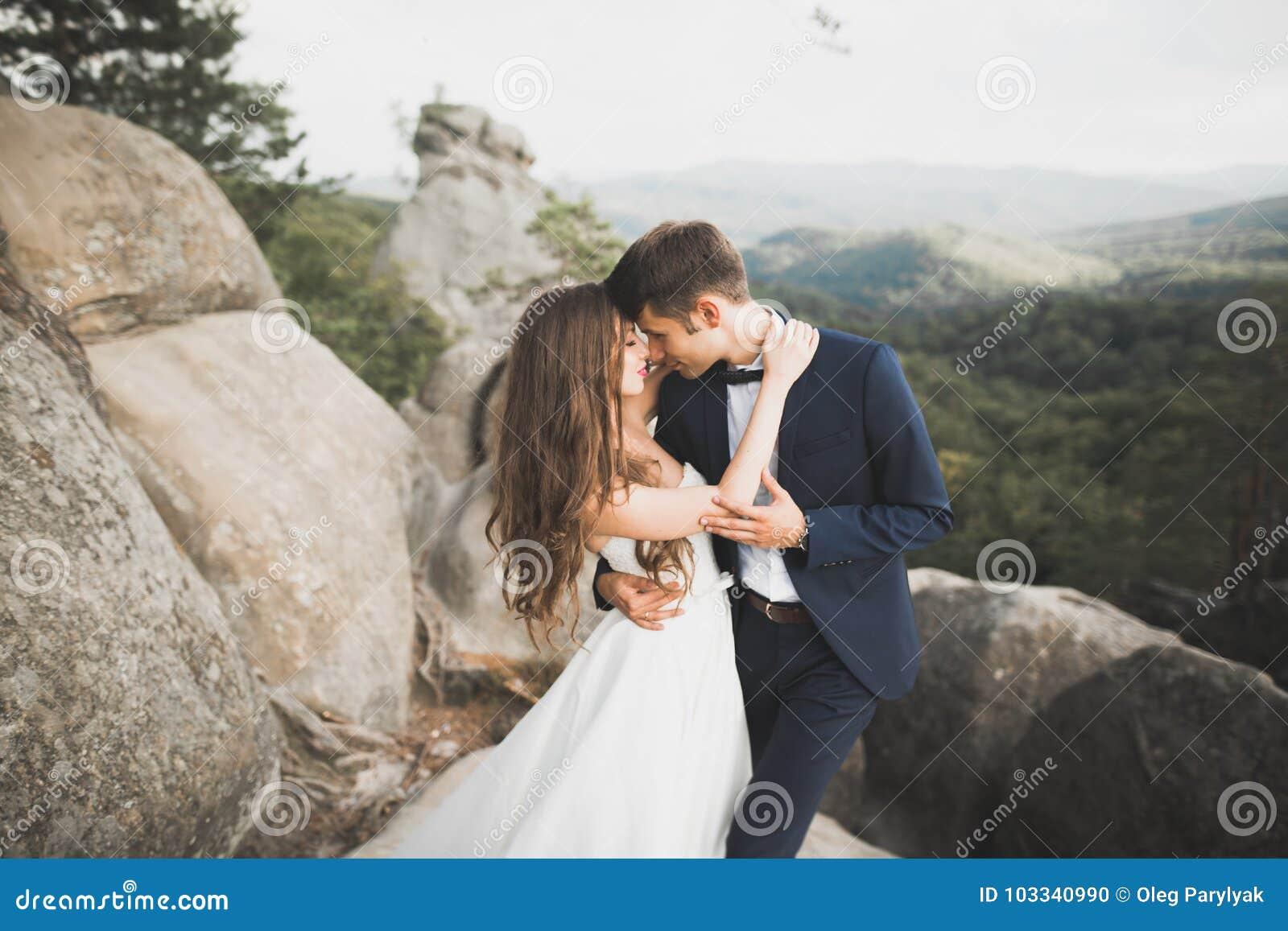 Πανέμορφη νύφη, νεόνυμφος που φιλά και που αγκαλιάζει κοντά στους απότομους βράχους με τις ζαλίζοντας απόψεις