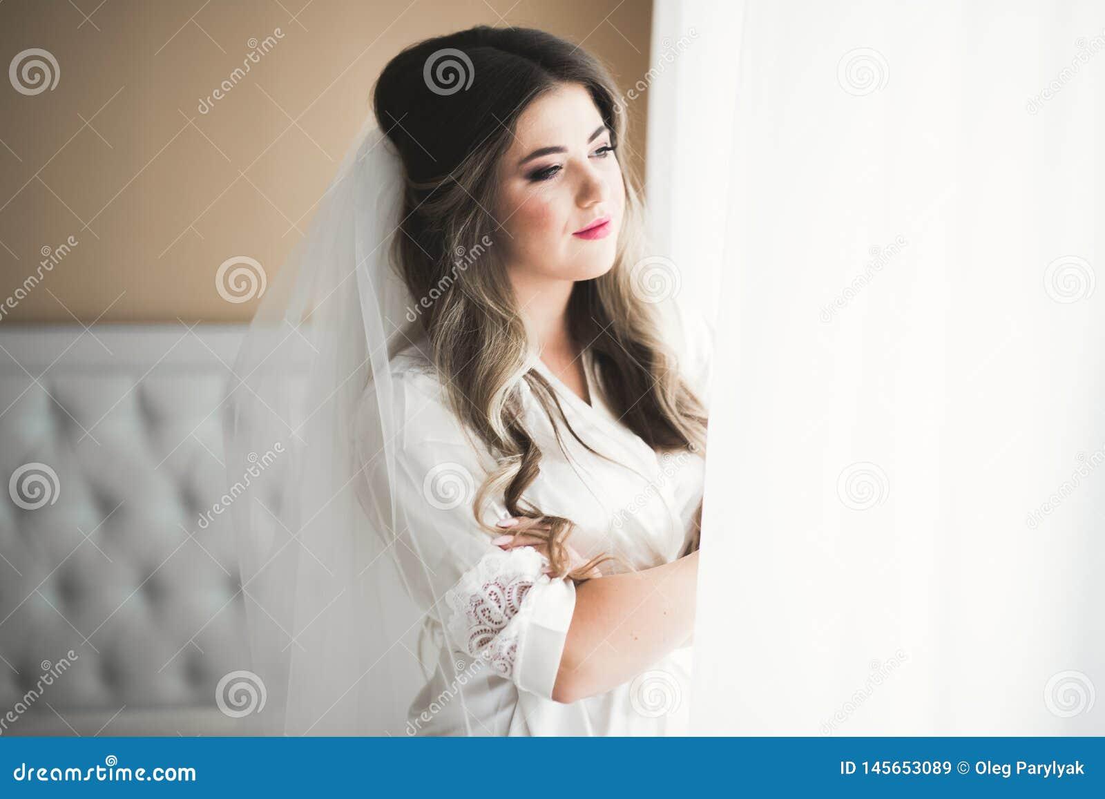 Πανέμορφη νύφη στην τήβεννο που θέτει και που προετοιμάζεται για το πρόσωπο γαμήλιας τελετής σε ένα δωμάτιο