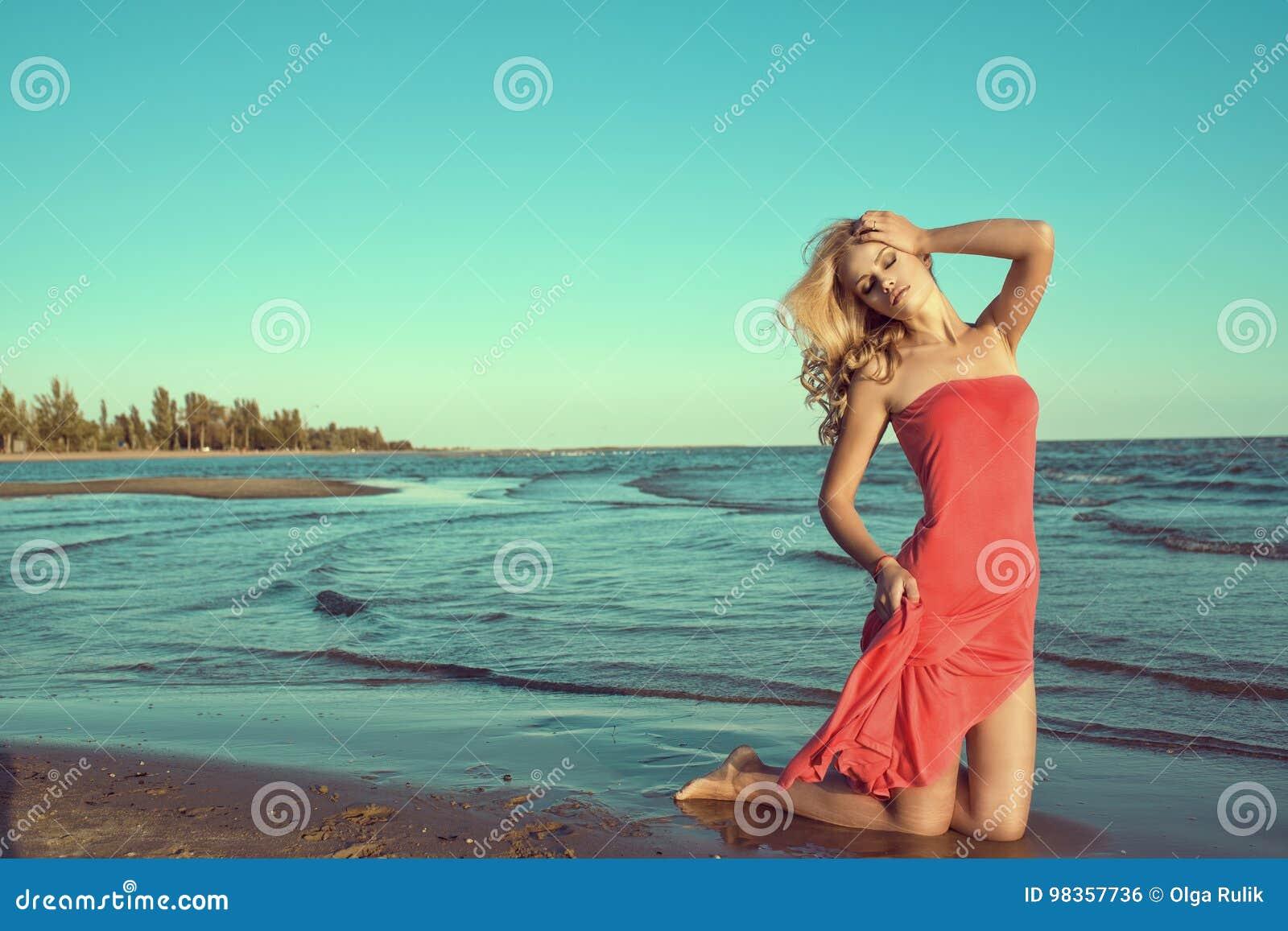 11649c3f5de7 Πανέμορφο προκλητικό λεπτό ξανθό πρότυπο στο κόκκινο στράπλες φόρεμα που  στέκεται στα γόνατα στο θαλάσσιο νερό