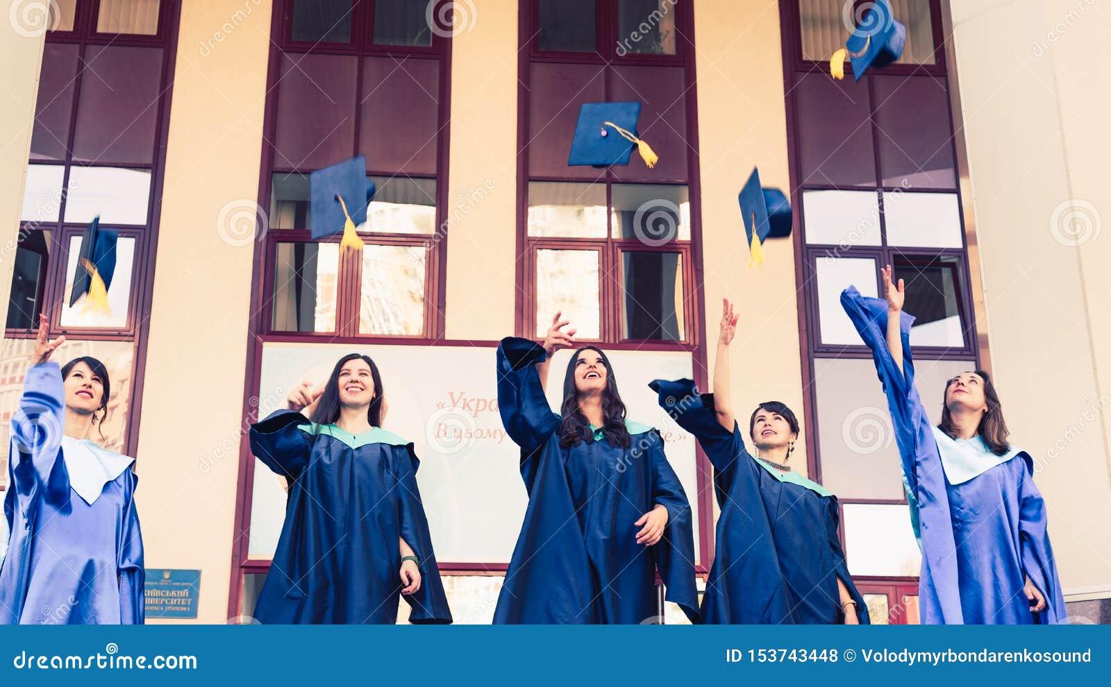 Πανεπιστημιακοί πτυχιούχοι που ρίχνουν τα καπέλα βαθμολόγησης στον αέρα Ομάδα ευτυχών πτυχιούχων στα ακαδημαϊκά φορέματα κοντά στ