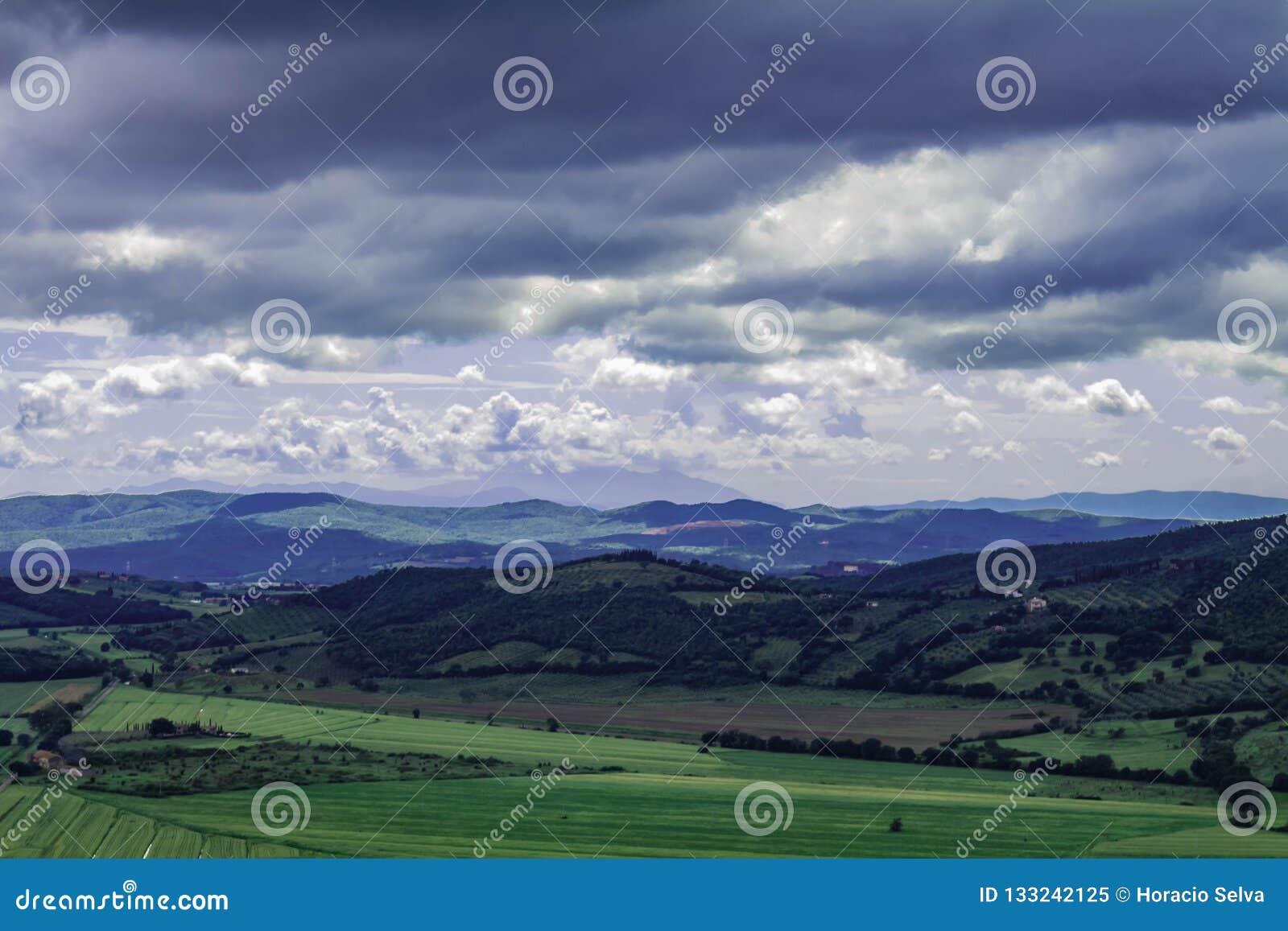 Πανοραμική άποψη της ιταλικής Τοσκάνης Τα βουνά στην απόσταση καλύπτονται από τα σύννεφα