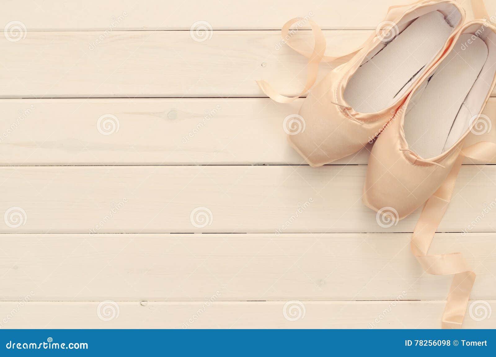 παπούτσια μεταξιού pointe στο άσπρο ξύλινο υπόβαθρο