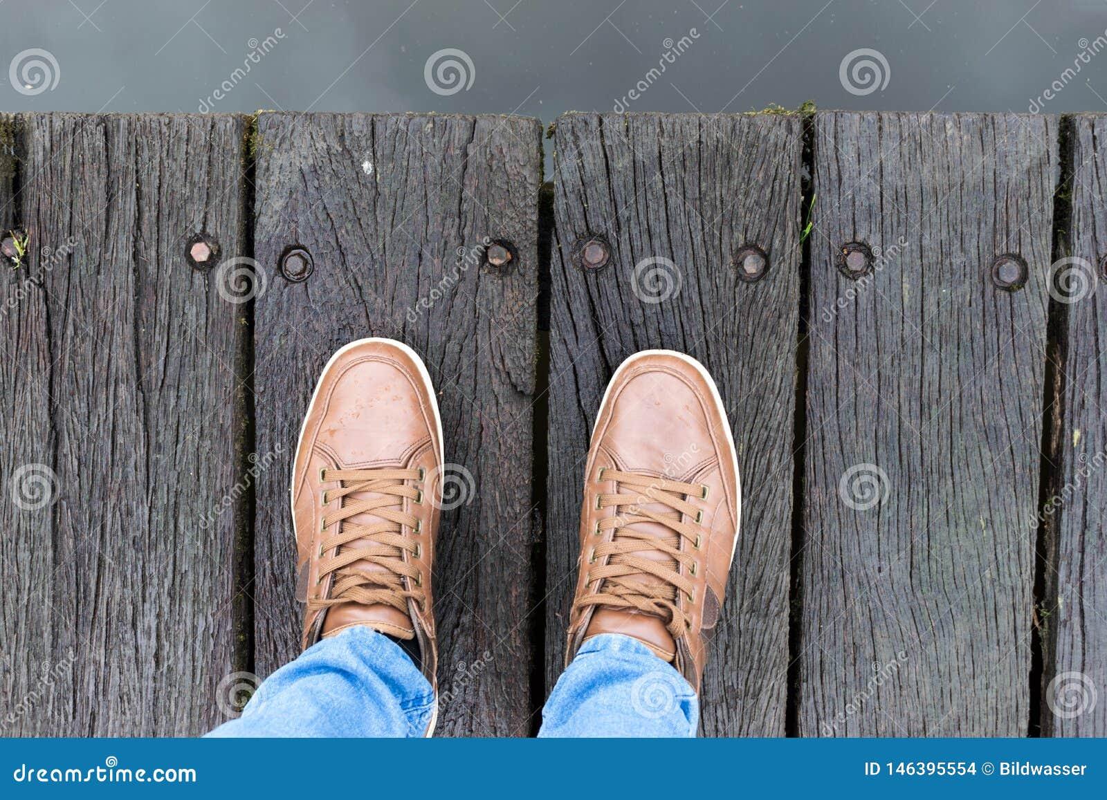 Παπούτσια πάνινων παπουτσιών που περπατούν στη βρώμικη ξύλινη τοπ άποψη
