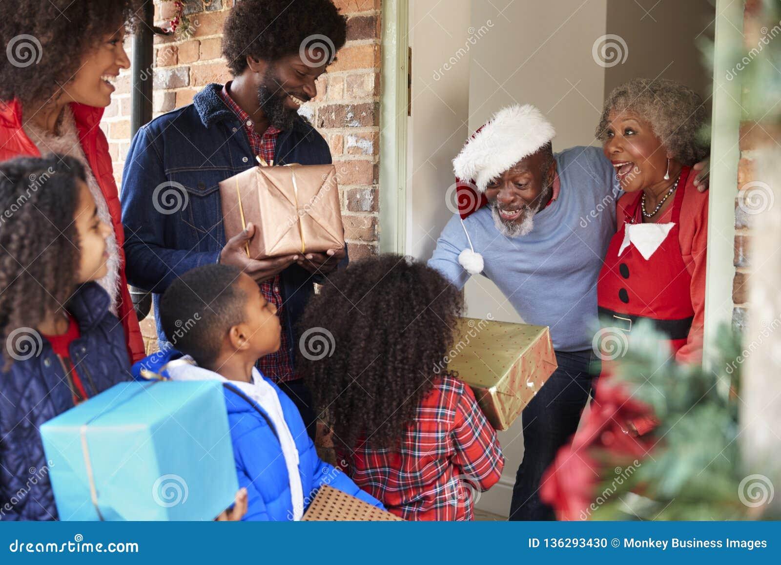 Παππούδες και γιαγιάδες που χαιρετούν την οικογένεια όπως φθάνουν για την επίσκεψη στη ημέρα των Χριστουγέννων με τα δώρα