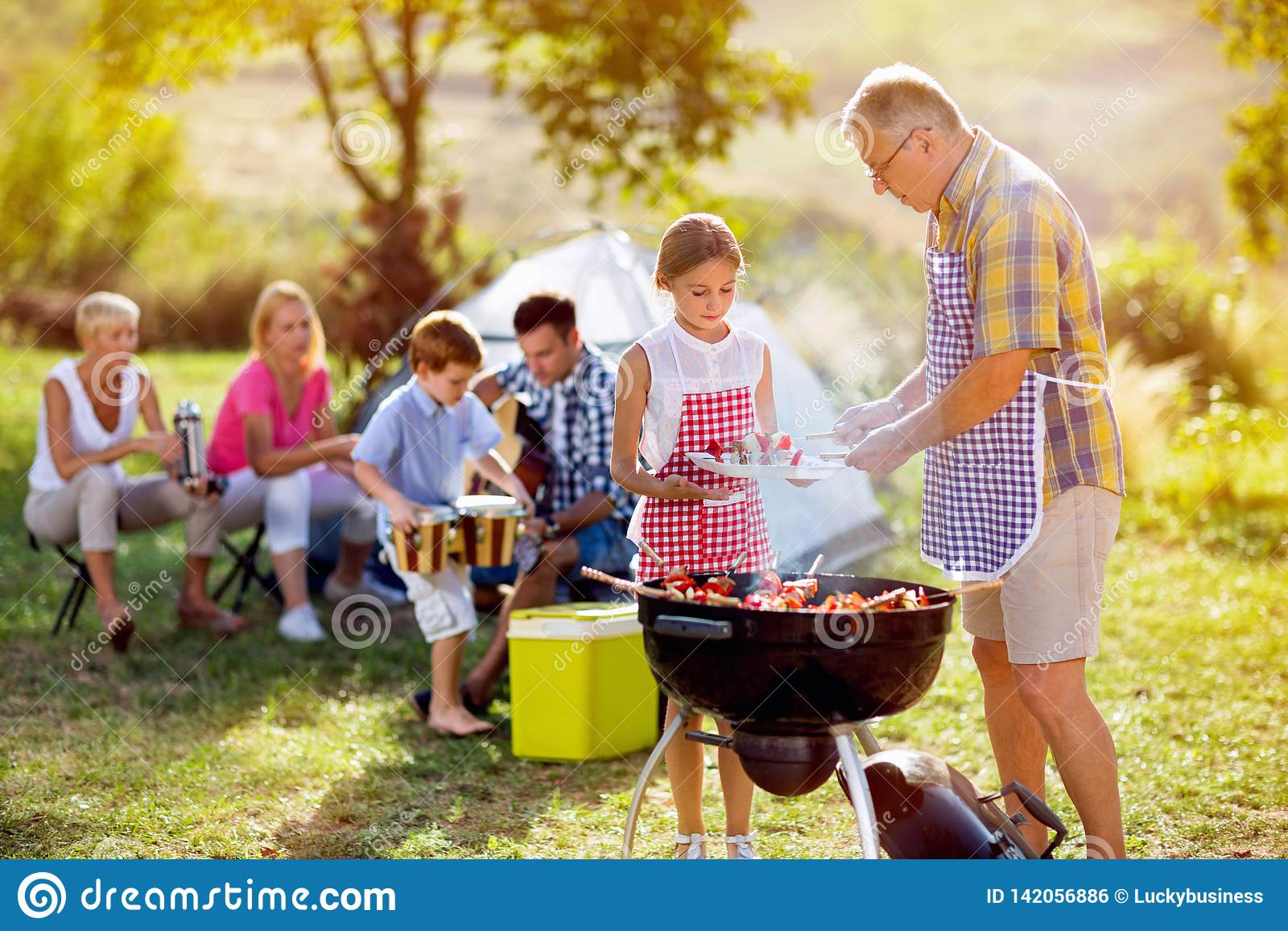 Παππούς που δίνει την εγγονή που ψήνει το κρέας στη σχάρα