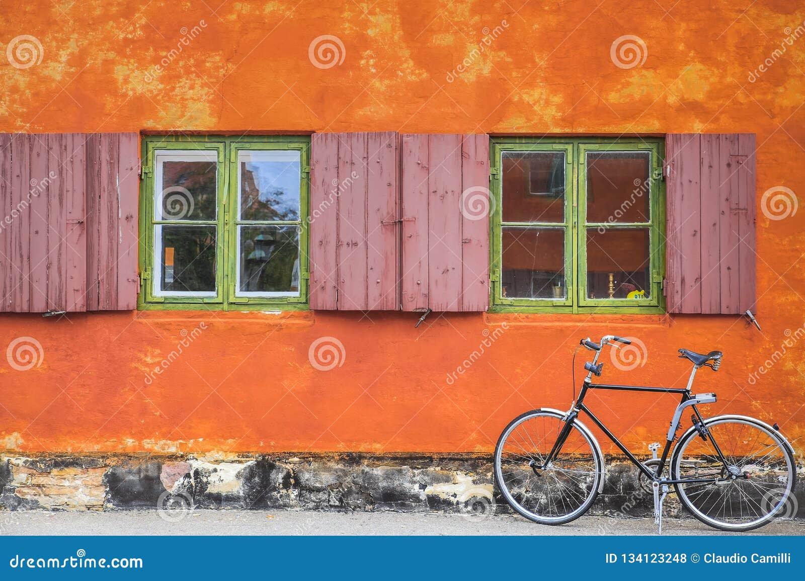 Παράθυρα με τον πορτοκαλή τοίχο και το εκλεκτής ποιότητας ποδήλατο