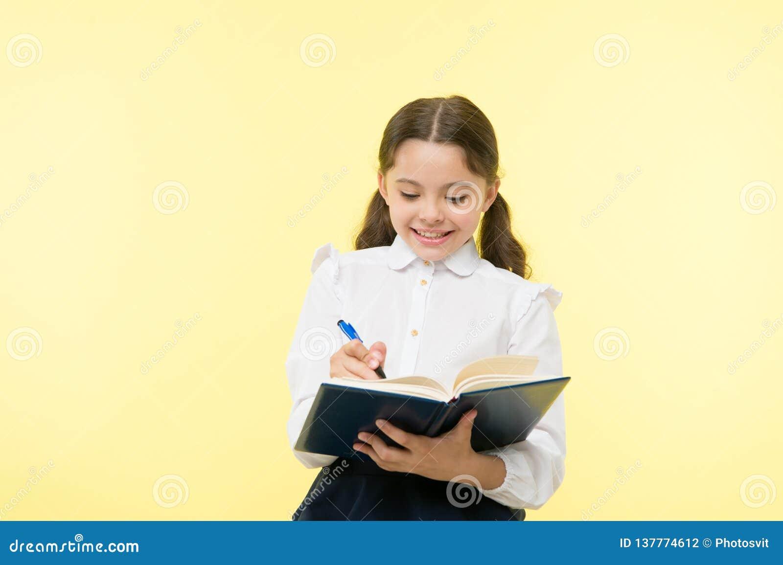 παραγωγή των σημειώσεων Παιδί σχολικών στολών παιδιών που κάνει την εργασία Βιβλίο και μάνδρα λαβής ενδυμάτων σχολικών στολών κορ