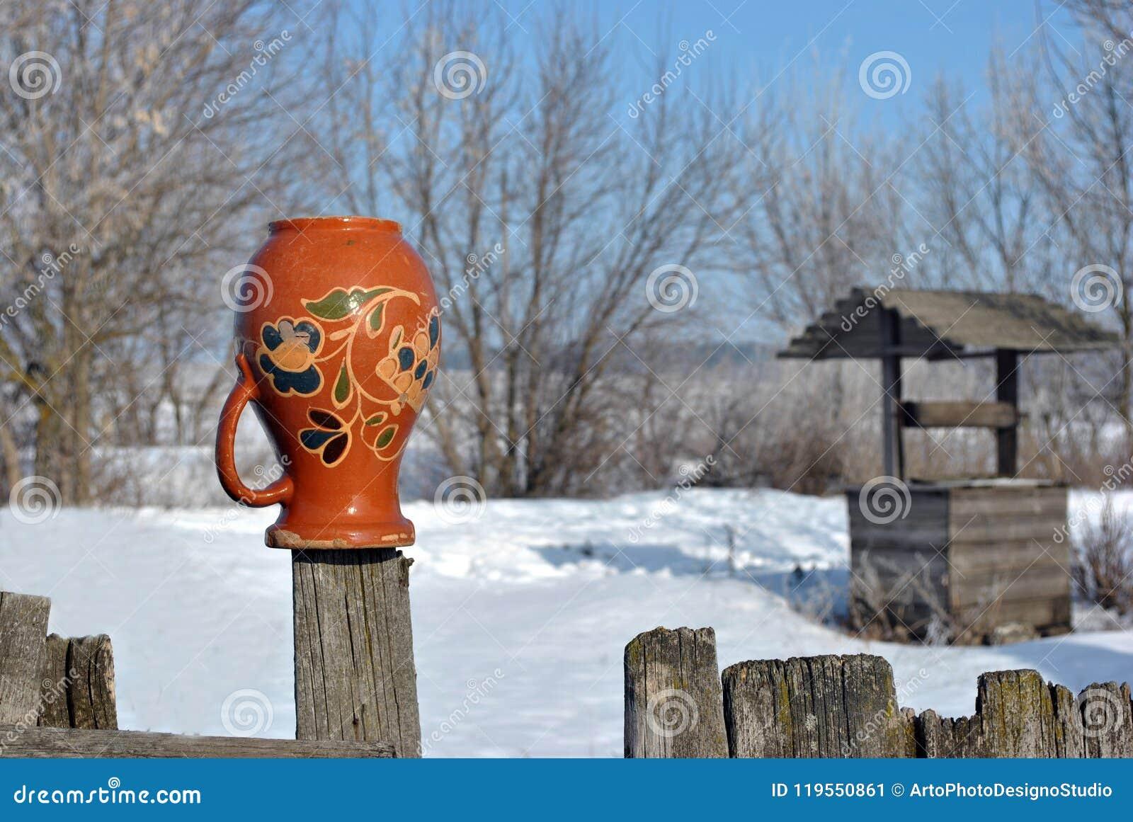 Παραδοσιακό ουκρανικό αγροτικό τοπίο με έναν ξύλινο καλά και φράκτης με την ένωση της στάμνας σε το με τη λαϊκή ζωγραφική Petryki