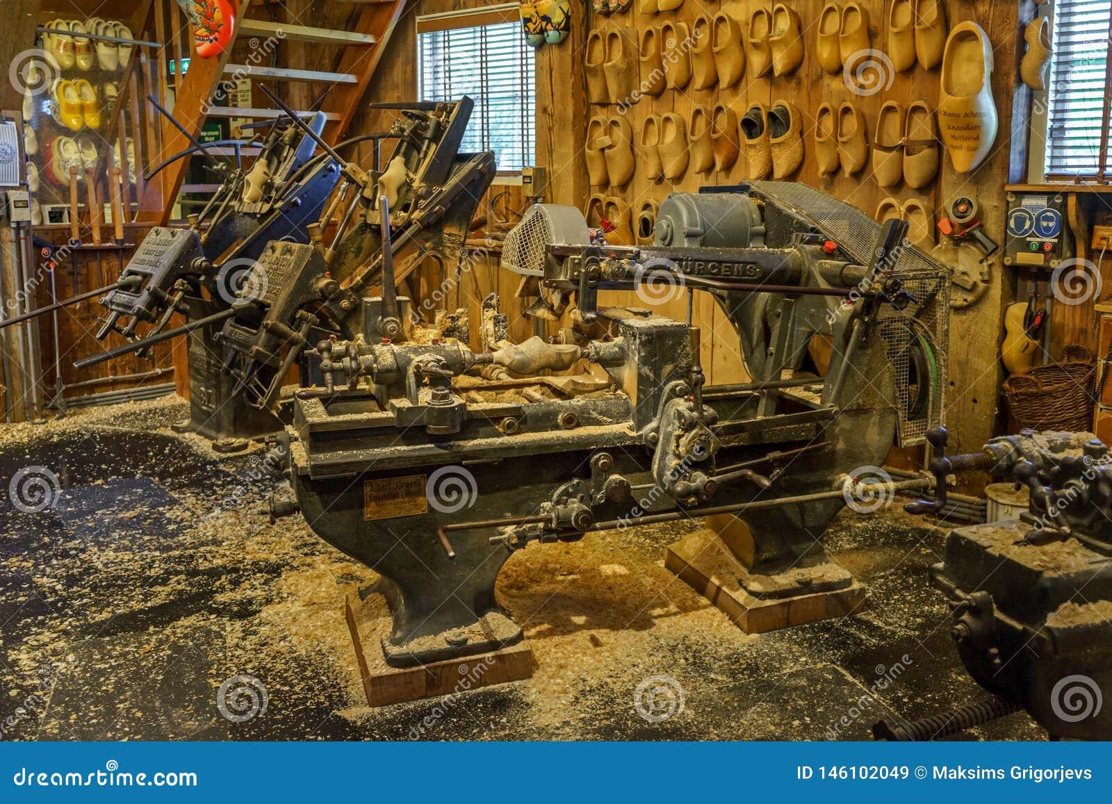 Παραδοσιακό παλαιό clog που κατασκευάζει τη μηχανή στο εργαστήριο με τα ξύλινα παπούτσια στην επίδειξη