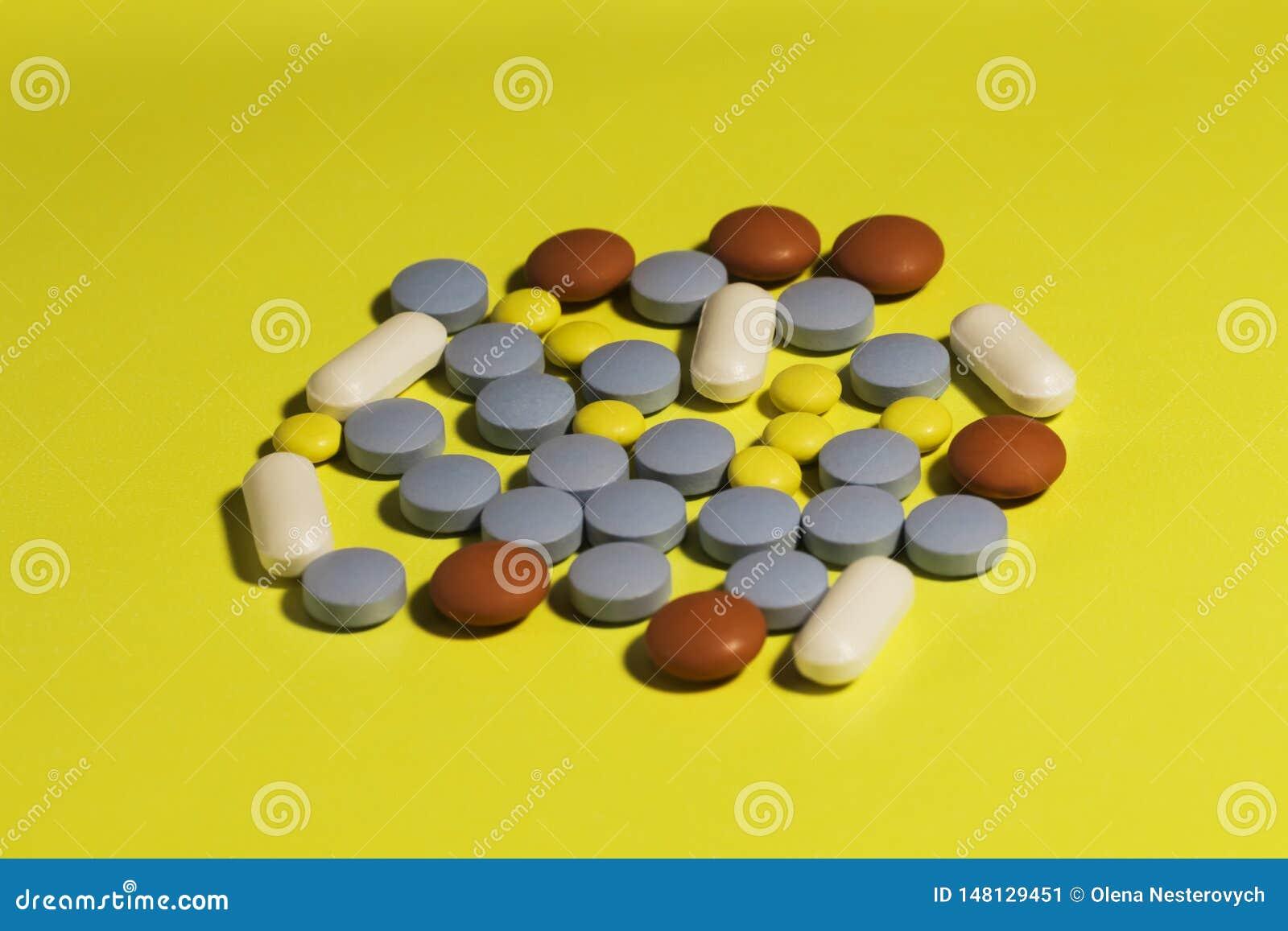 Παραλήπτης της ιατρικής και πολλά χάπια που απομονώνονται στο κίτρινο υπόβαθρο, έννοια της υγείας