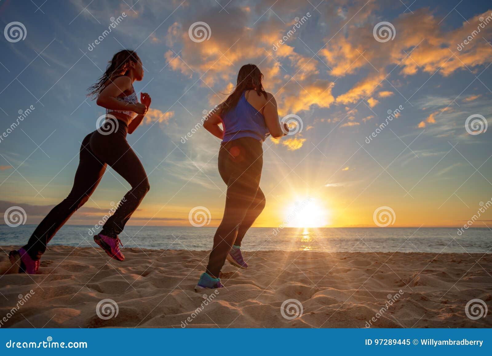 Παραλία δύο ηλιοβασιλέματος κατάλληλα κορίτσια jogginr στην άμμο
