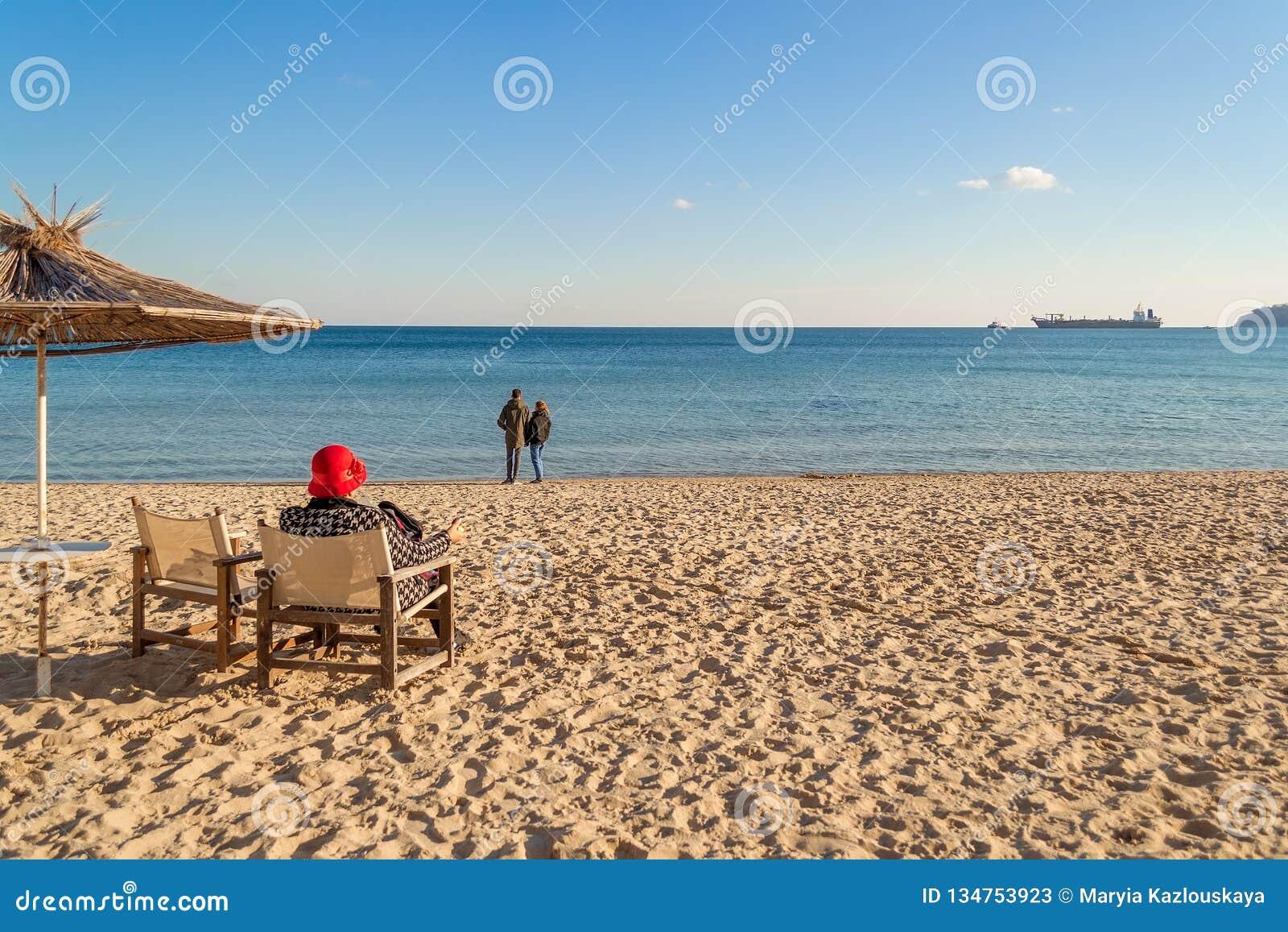Παραλία χειμερινής θάλασσας και ήρεμη θάλασσα μια ηλιόλουστη ημέρα Μια μόνη ηλικιωμένη γυναίκα κάθεται σε μια καρέκλα γεφυρών που