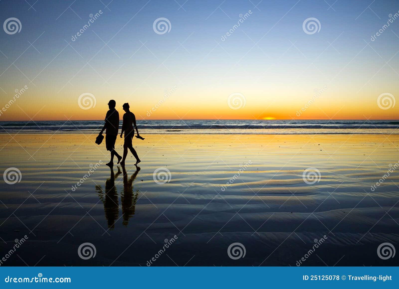 παραλιών περπατώντας νεολαίες ηλιοβασιλέματος ζευγών ρομαντικές