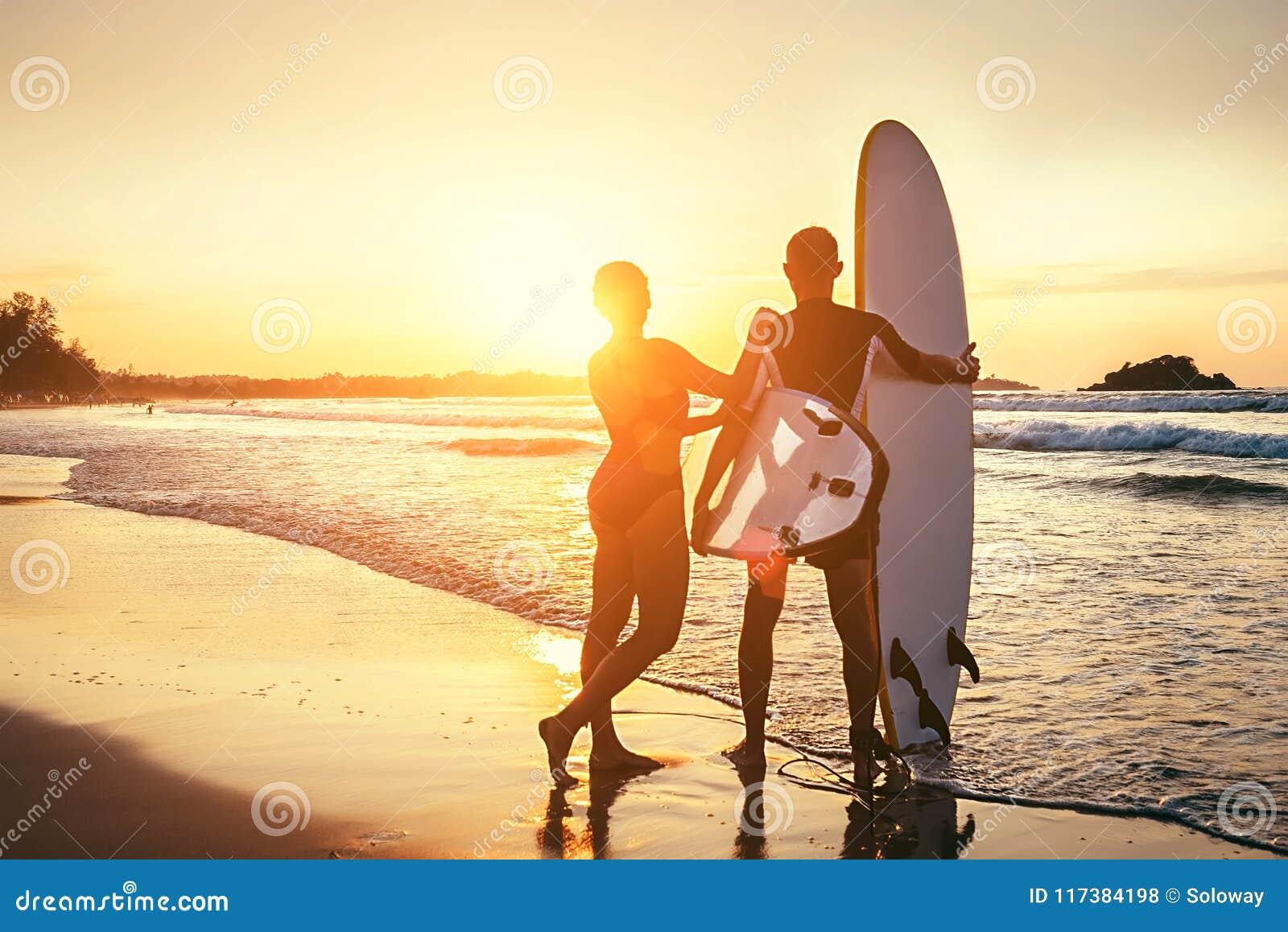 Παραμονή surfers ζεύγους στην ωκεάνια παραλία ηλιοβασιλέματος