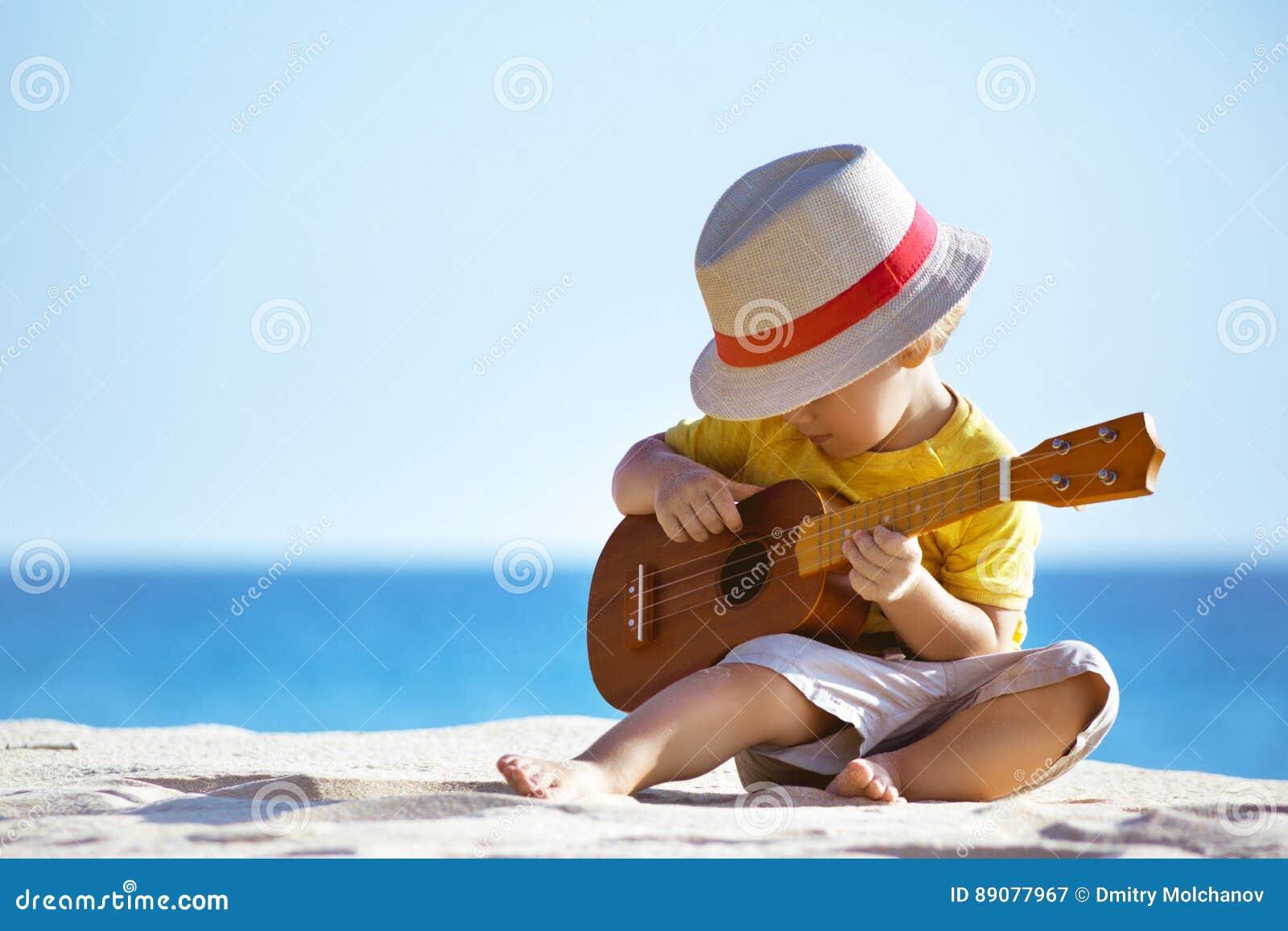 Παραλία κιθάρων παιχνιδιών μικρών παιδιών ukulele εν πλω