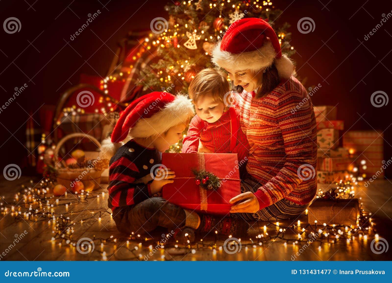 Παρόν κιβώτιο δώρων φωτισμού οικογενειακού ανοίγματος Χριστουγέννων κάτω από το χριστουγεννιάτικο δέντρο, την ευτυχή μητέρα και τ