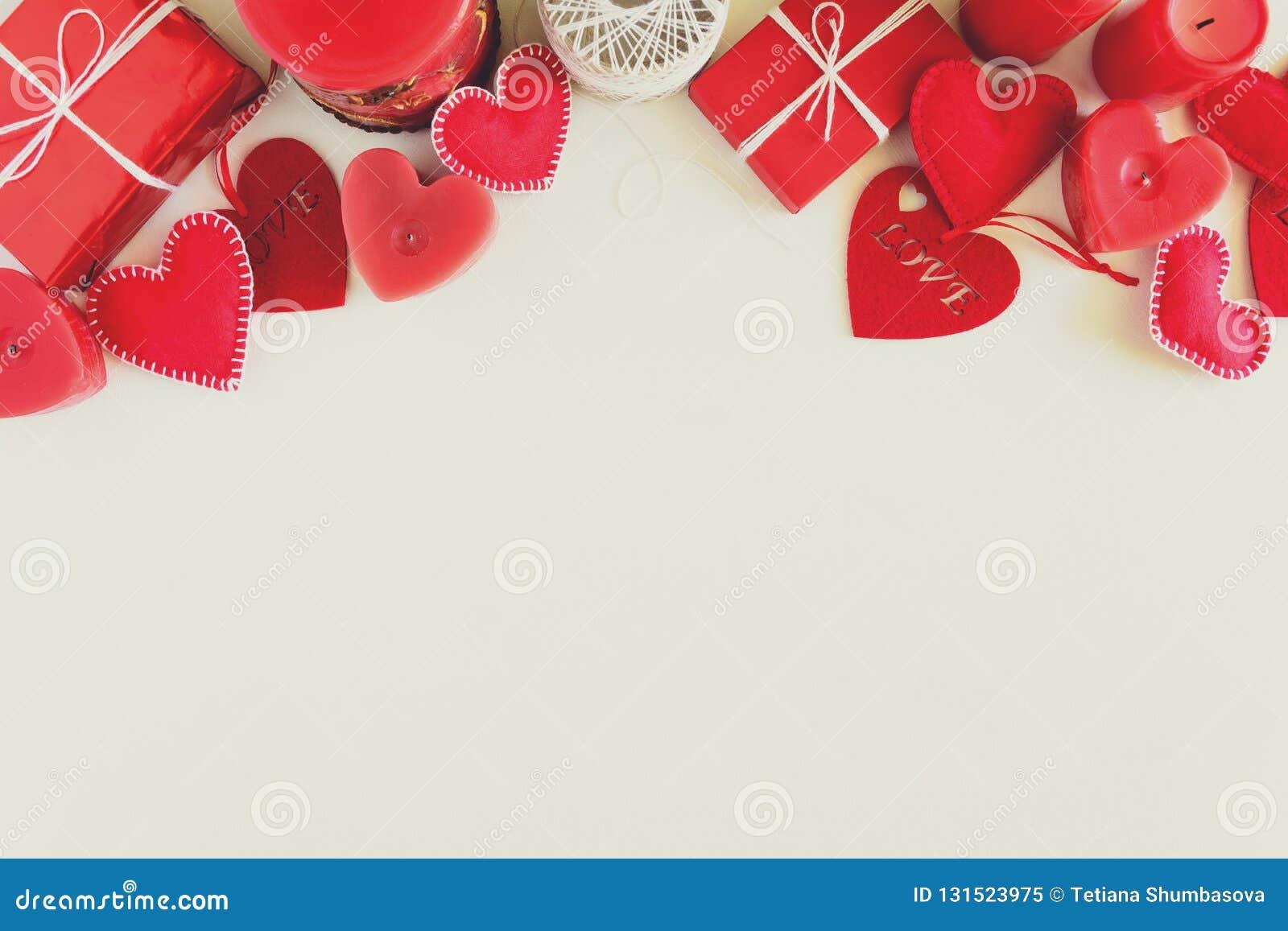 Παρόν κιβώτιο με τις αισθητά καρδιές και τα κεριά αγάπης στο άσπρο ξύλινο υπόβαθρο Έννοια εορτασμού ημέρας βαλεντίνων ` s Τοπ όψη