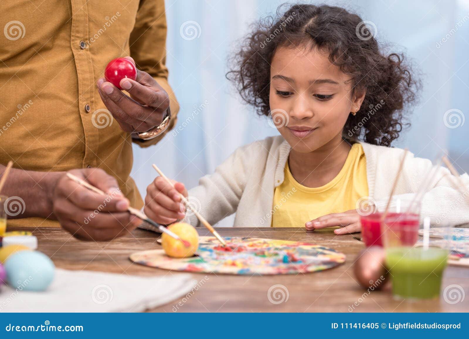 Πατέρας αφροαμερικάνων και λατρευτή κόρη που χρωματίζουν τα αυγά Πάσχας με τα χρώματα αφισών