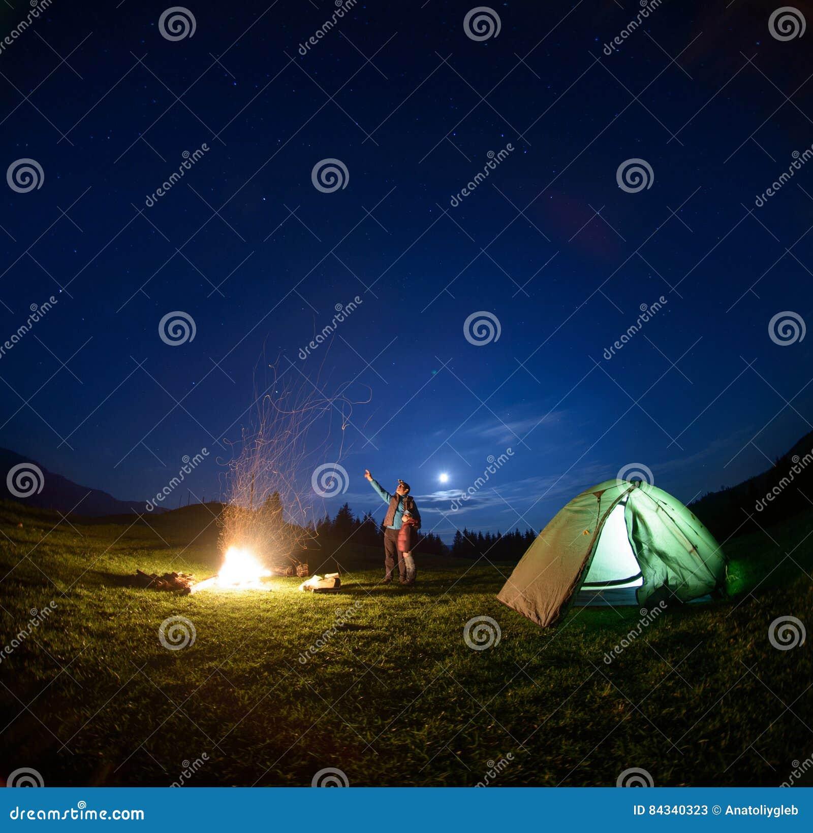 Πατέρας και γιος κοντά στην πυρά προσκόπων και σκηνή κάτω από το νυχτερινό ουρανό