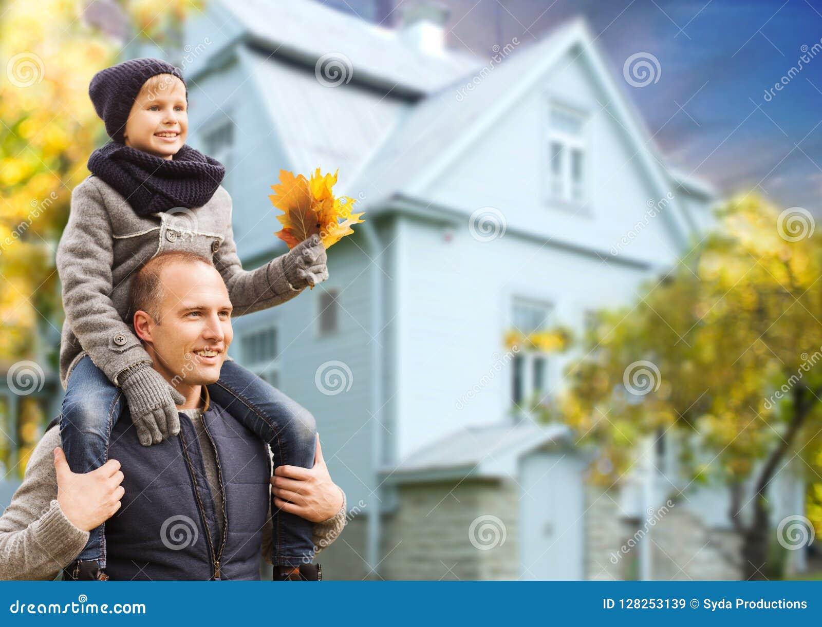 Πατέρας και γιος με τα φύλλα σφενδάμου φθινοπώρου πέρα από το σπίτι