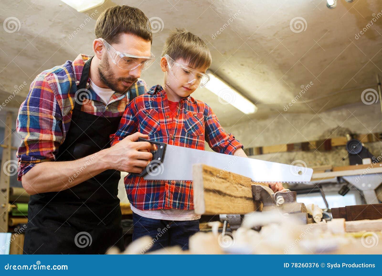 Πατέρας και γιος με το πριόνι που λειτουργεί στο εργαστήριο
